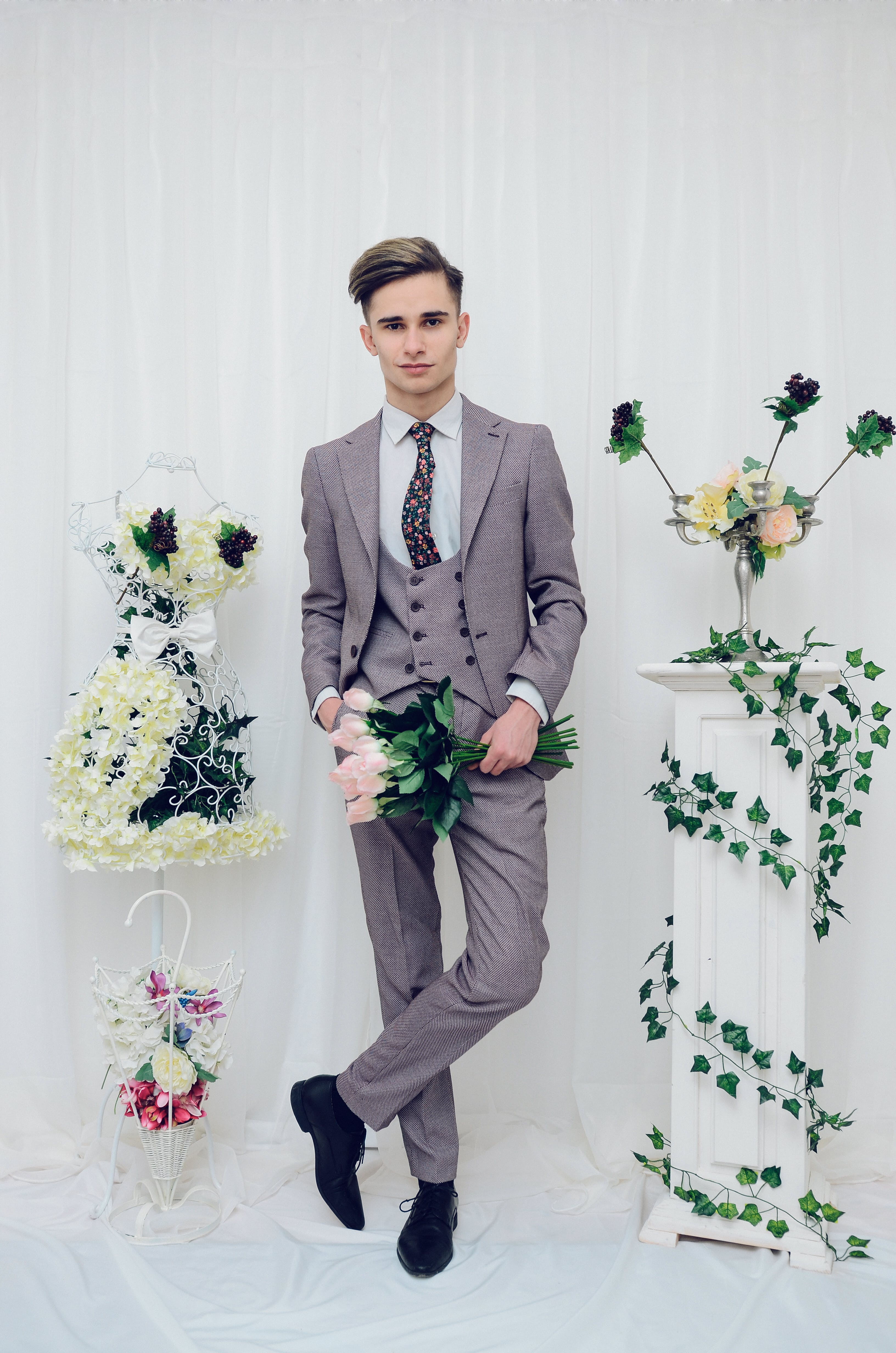 Smiling Man Standing Between Flowers Holding Pink Flowers Bouquet