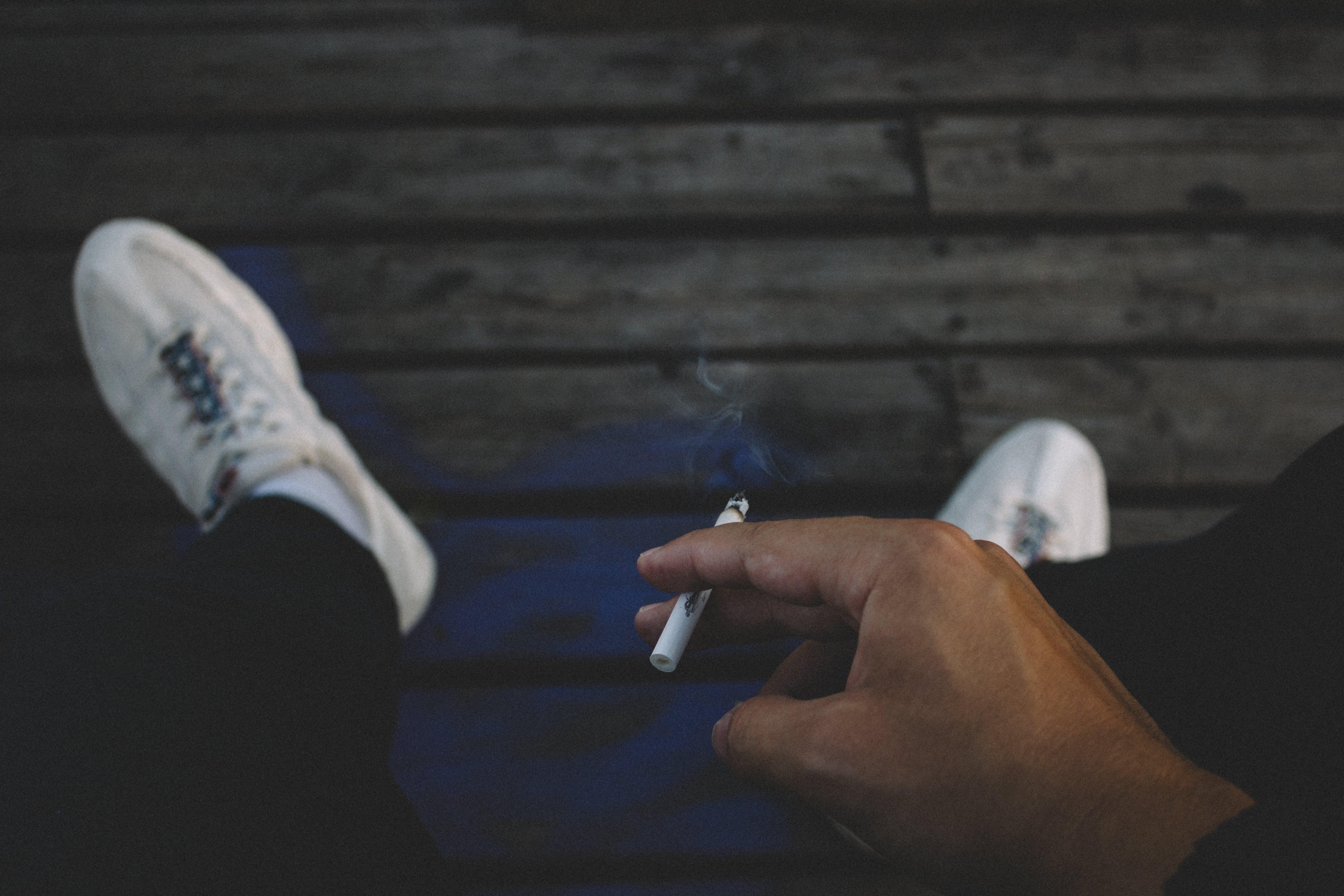 Person Holding Cigarette Stick