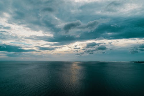 Picturesque view of rippled ocean with horizon line under sky with clouds in twilight