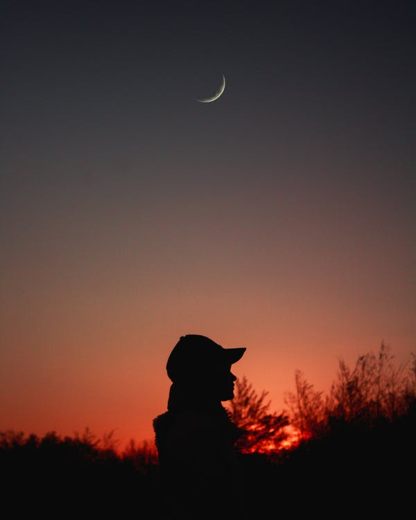 Silhouette of Person Wearing Cap Under Crescent Moon