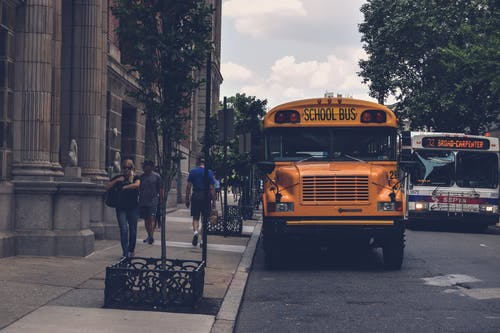 Yellow School Bus Beside Gray Concrete Building