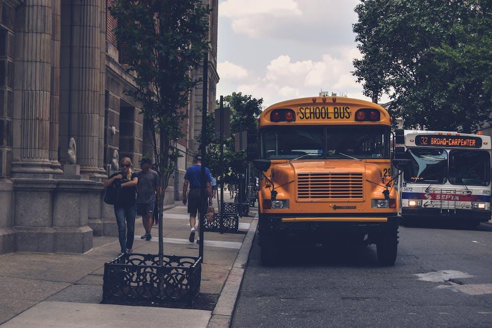 Yellow school bus beside a concrete building.   Photo: Pexels