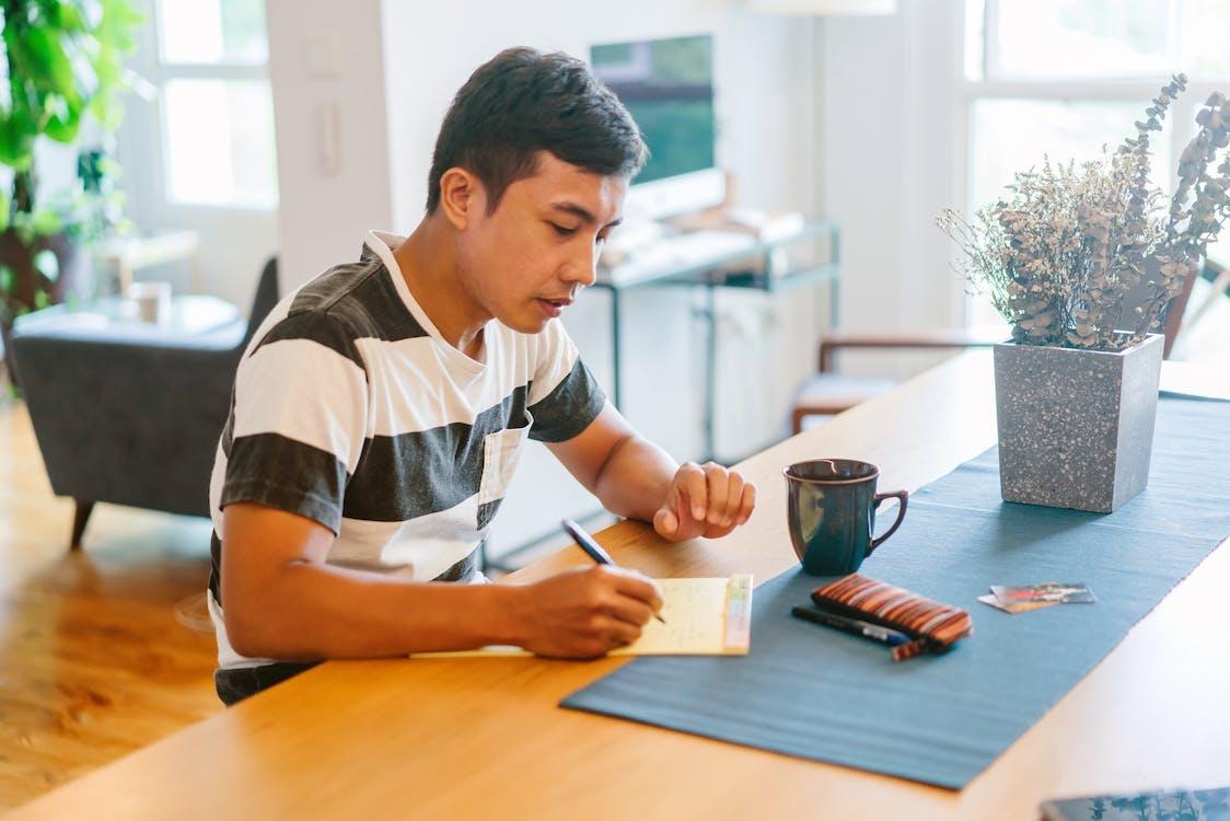 Man Writing on Notepad Inside House