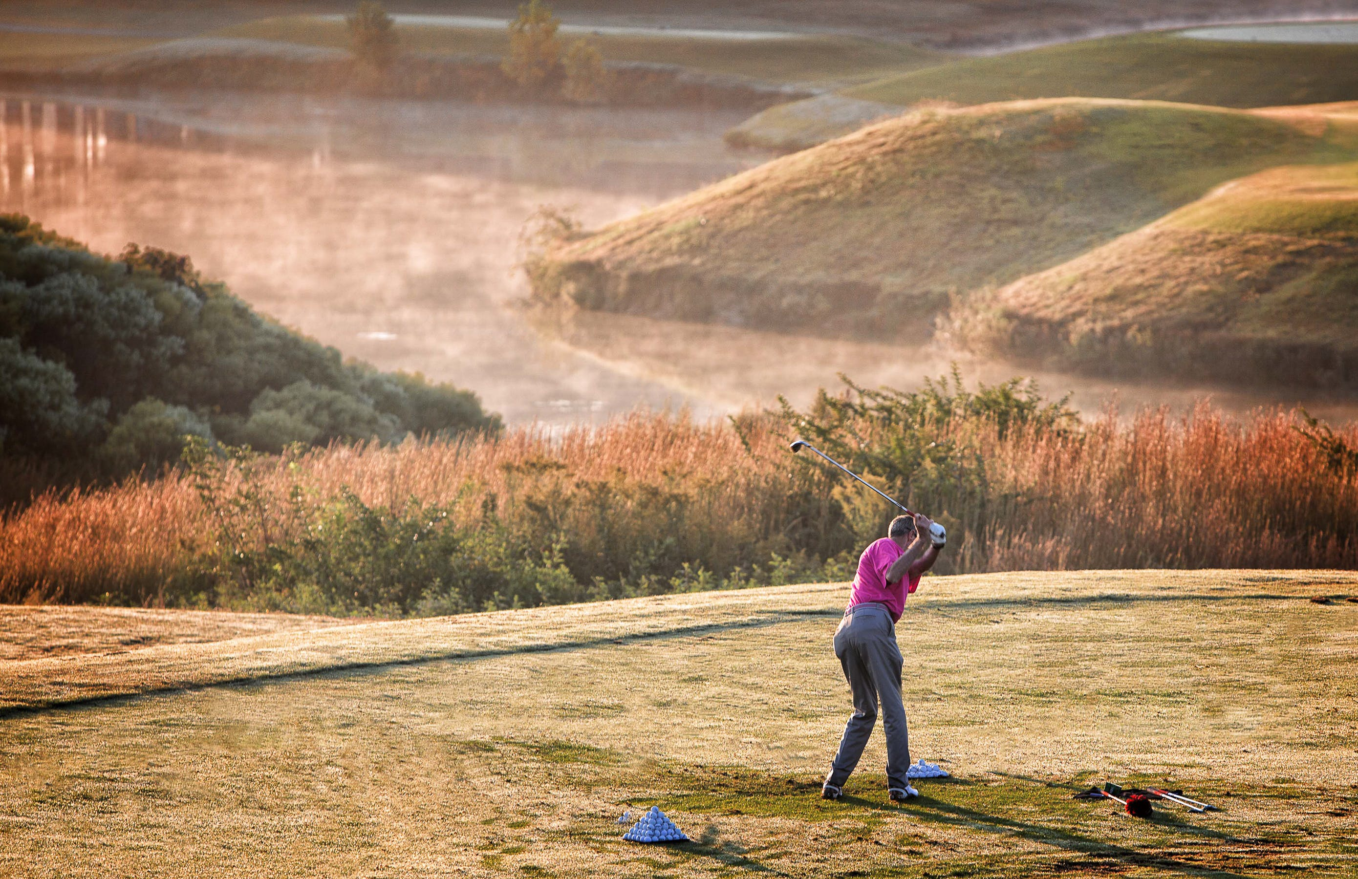 Photo of Person Wearing Pink T-shirt and Grey Dress Pants Swinging Golf Club