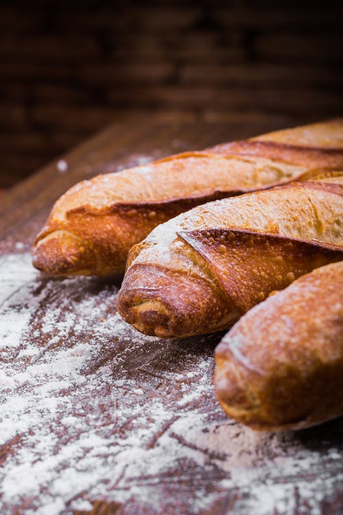 Close-up Photo of Three Baguettes on Brown Wooden Surface With White Powder