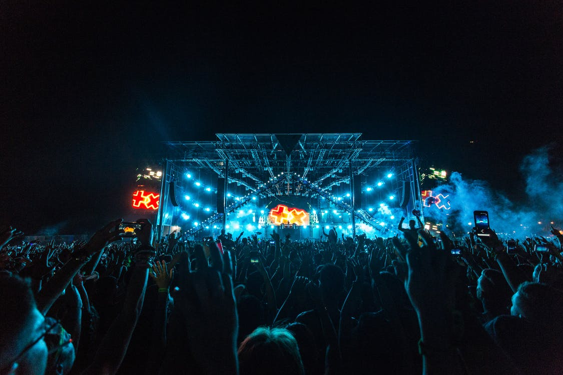 Crowd in Front of Blue and Orange Stage during a Concert at Night