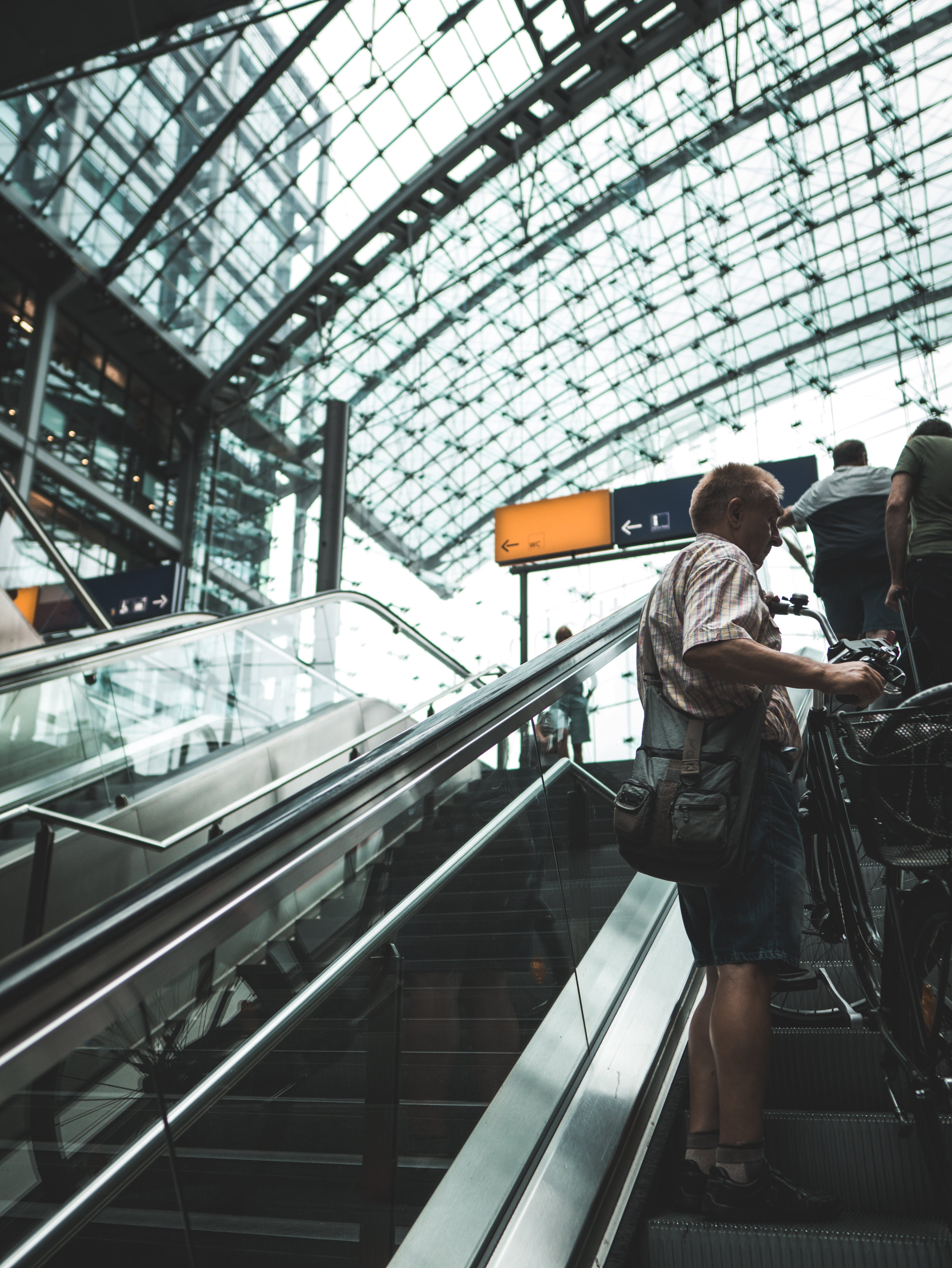 Man Standing On Escalator Holding Bike
