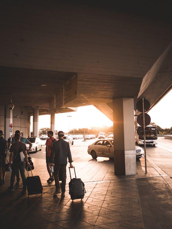 الرجال سحب حقائب الأمتعة على طول مدخل المطار