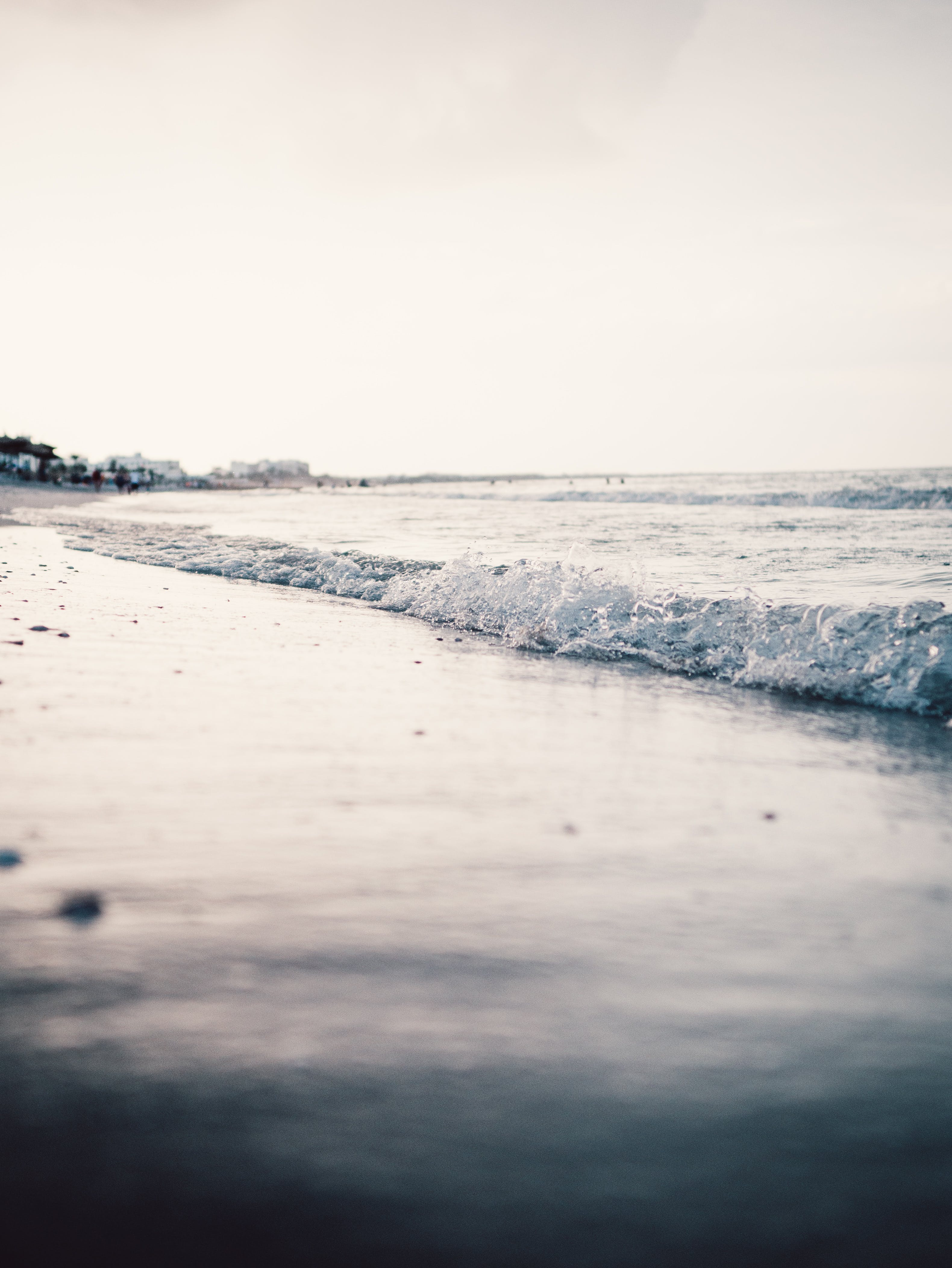 Landscape Photography of Seashore With Calm Sea Waves Under Gray Skies