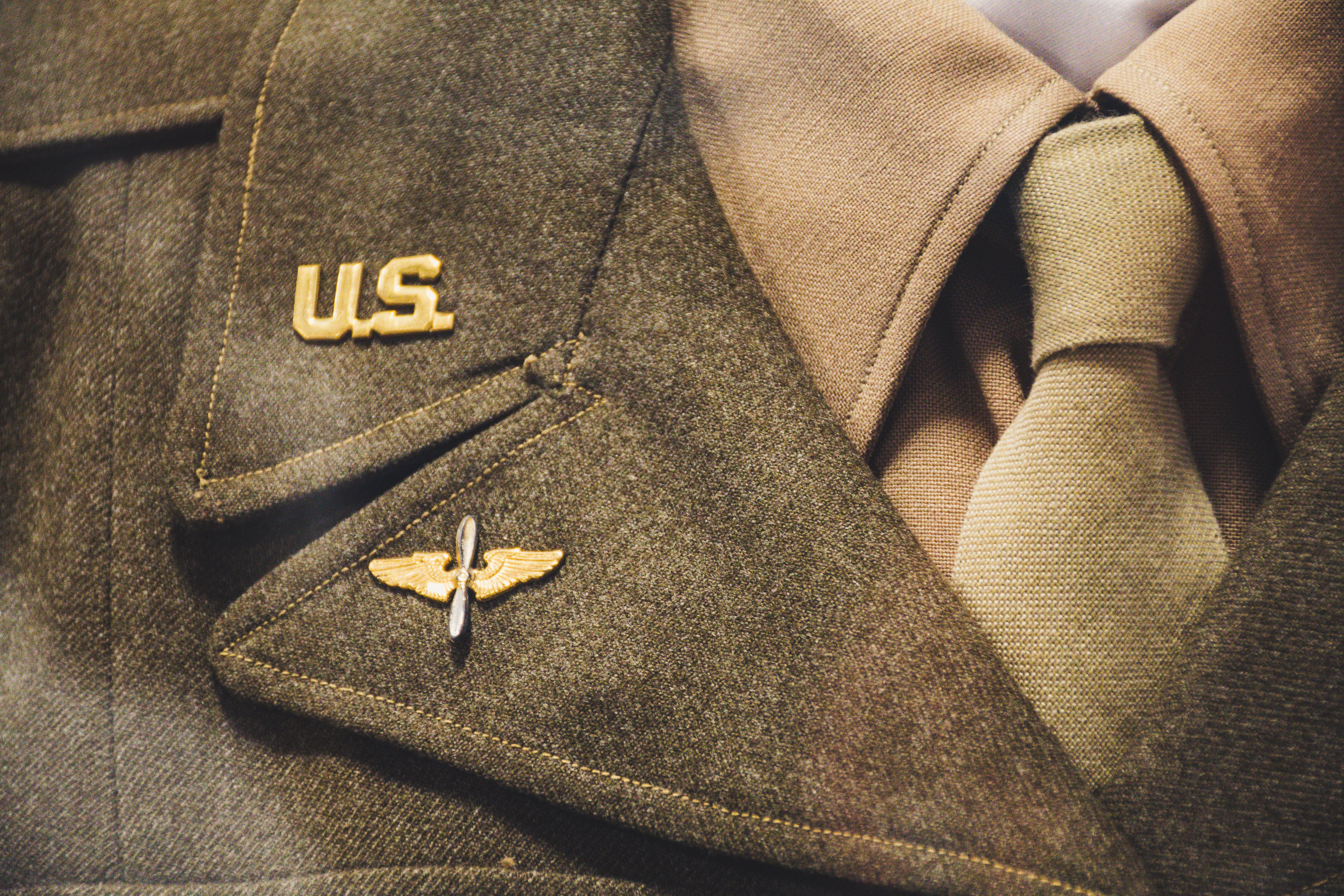 Gold-colored Us Brooch on Apparel