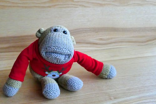 Gray Monkey Amigurumi Doll Wearing Red Sweater on Brown Wooden Surface