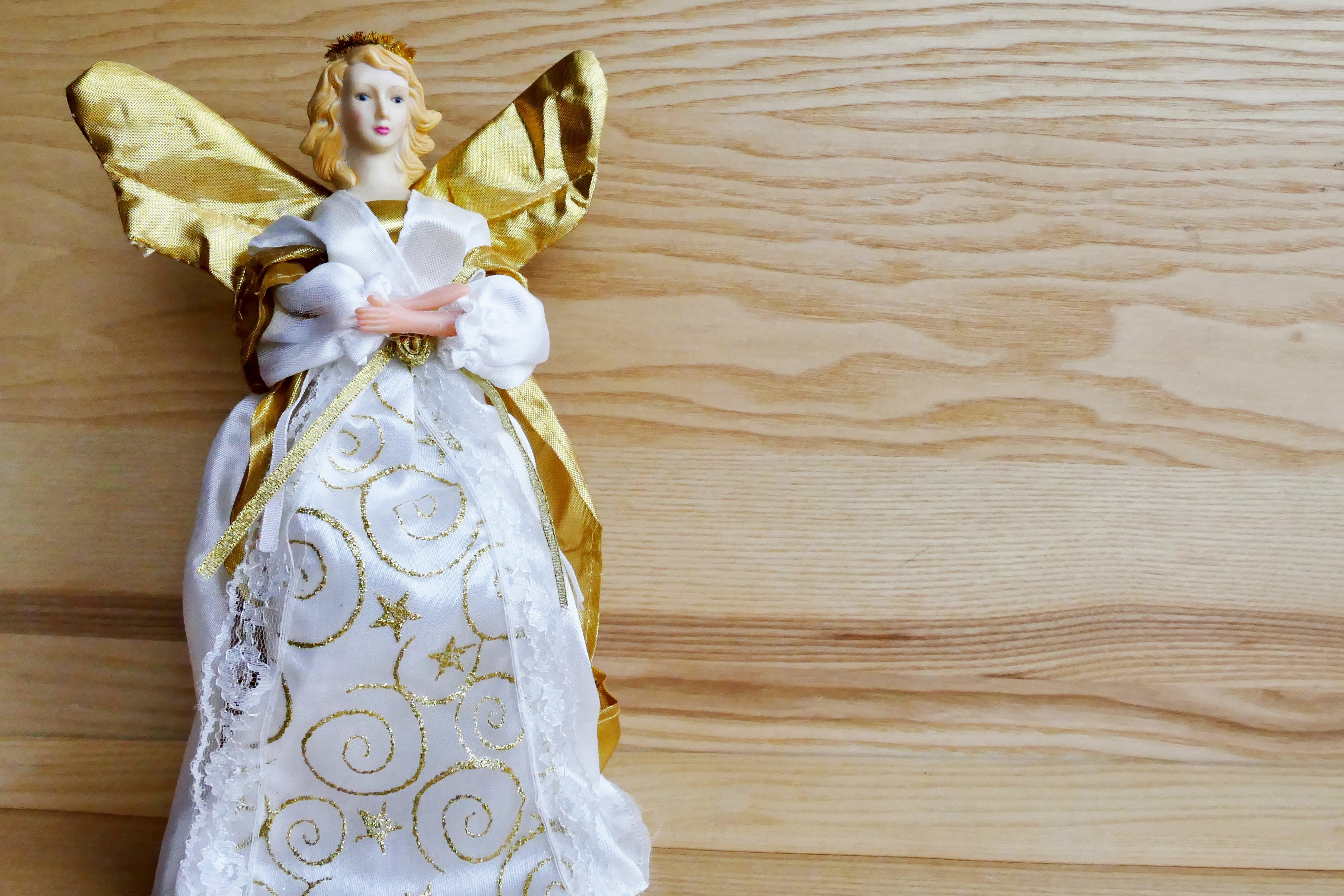 Angel Ceramic Figurine on Beige Wooden Surface