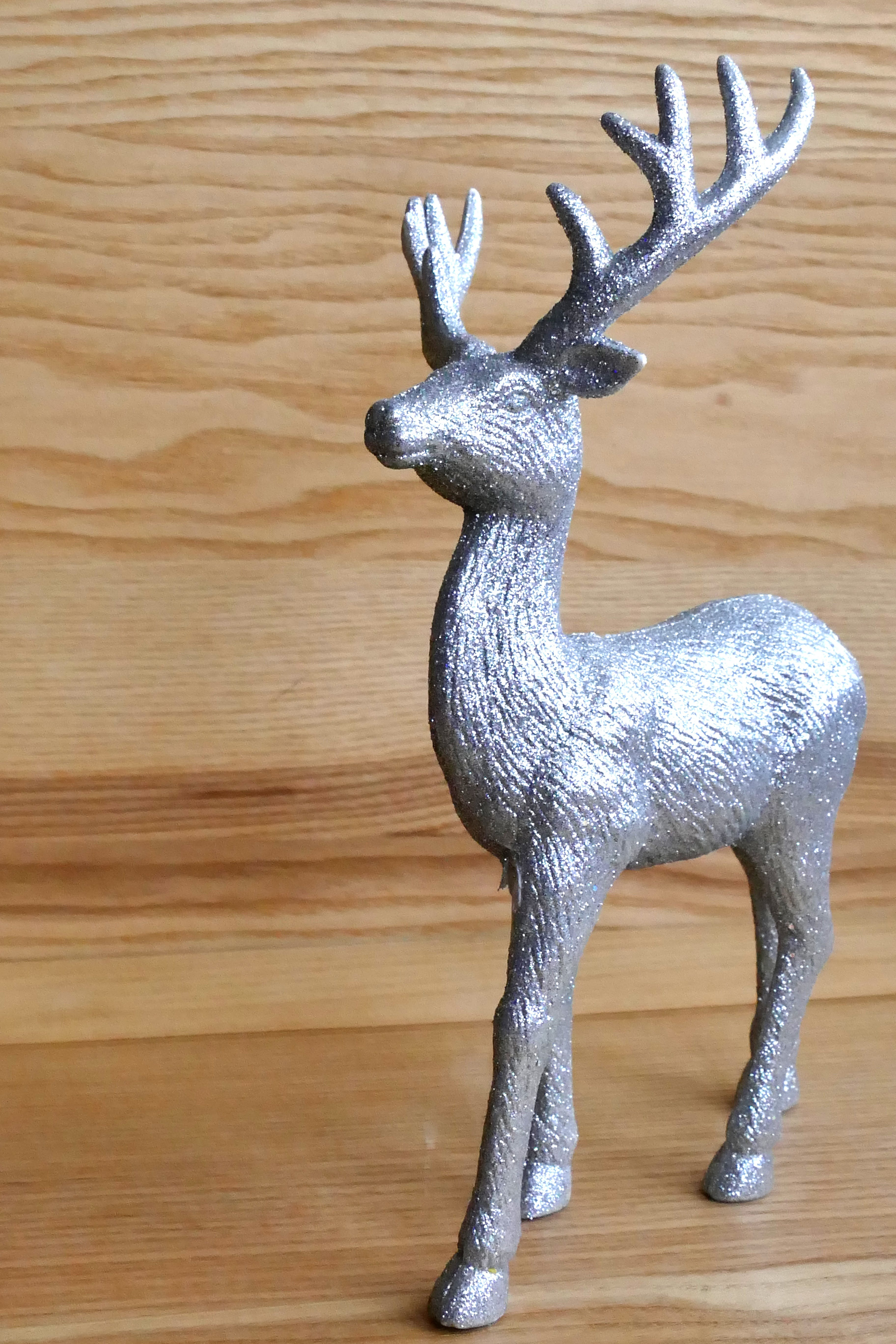 Gray Deer Figurine on Wooden Surface