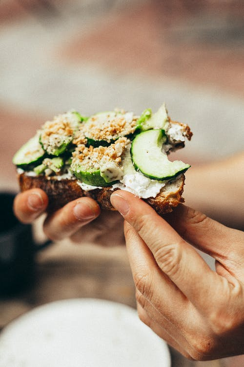 Person Holding Bitten Bread With Green Vegetables