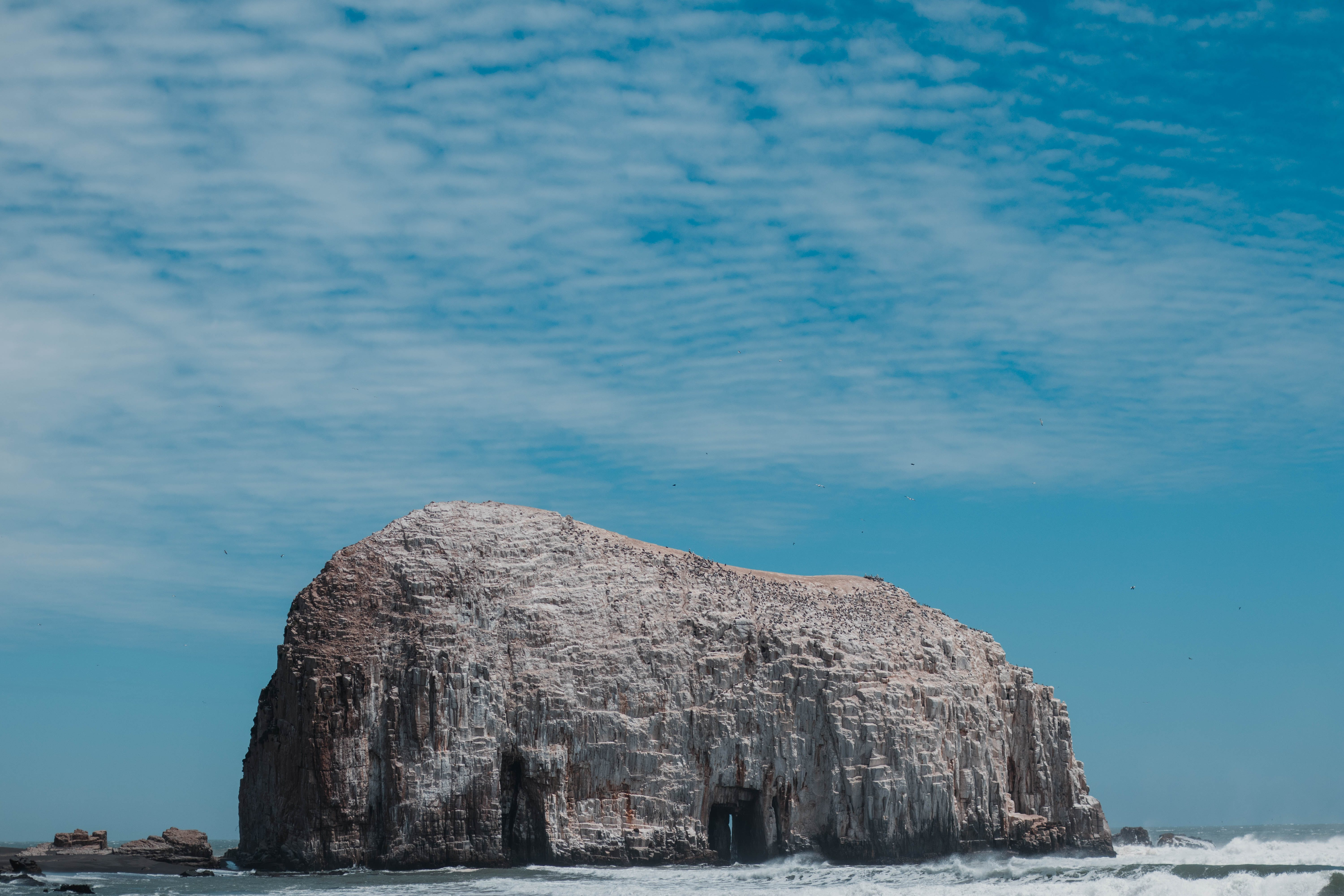 Gray Rock Formation on Beach Under Blue Sky