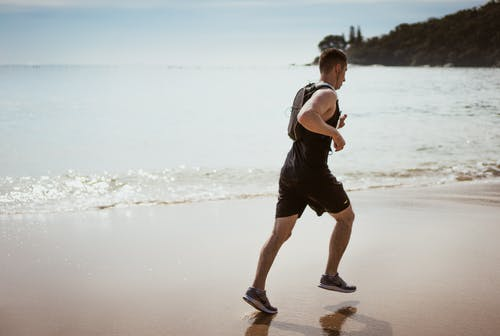 Man Wearing Black Tank Top and Running on Seashore