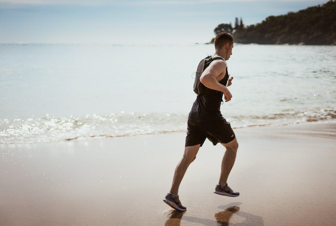 Man Wearing Black Tank Top and Running on Seashore