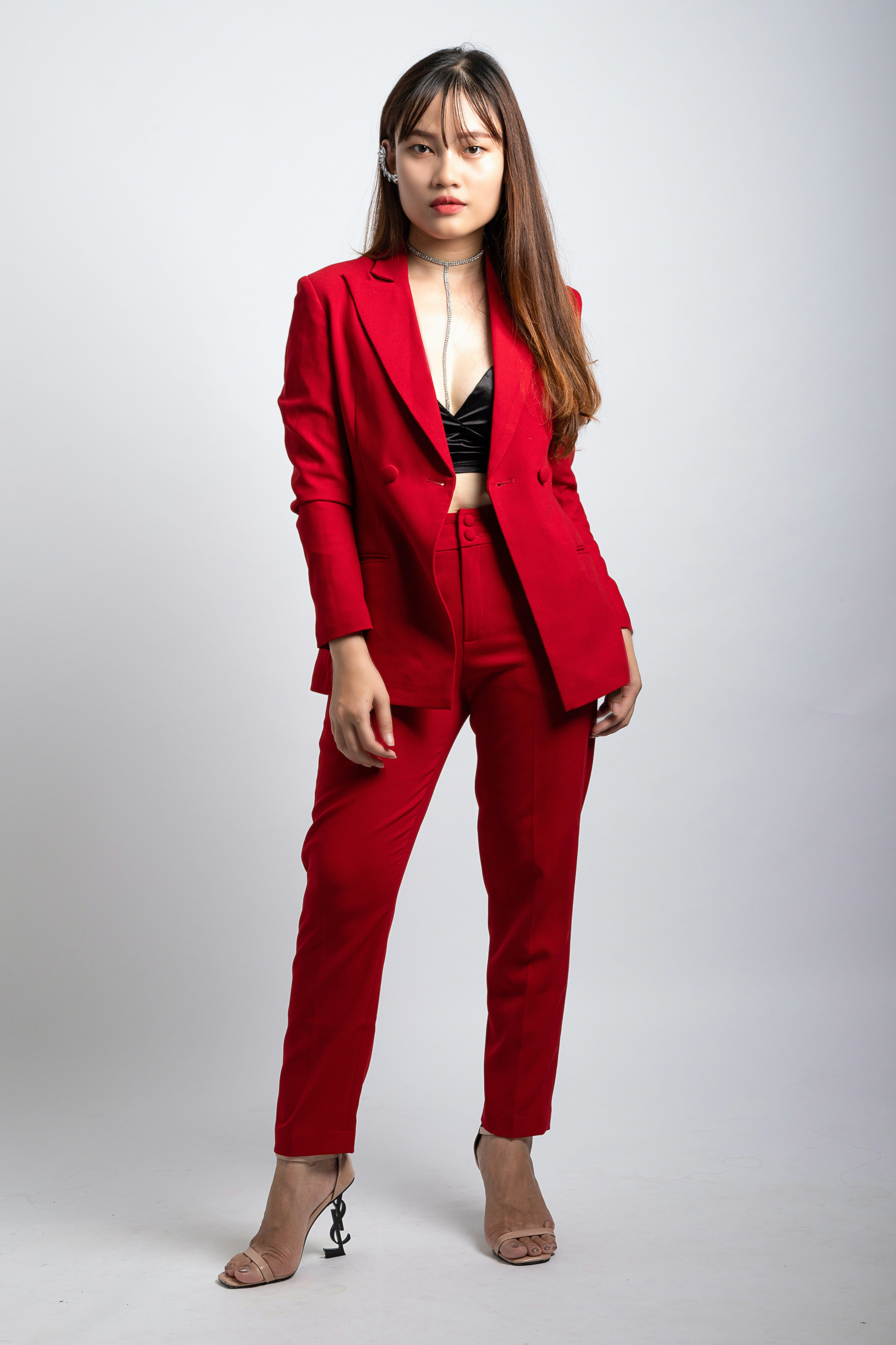 Woman Wearing Red Coat and Dress Pants Standing in Front of White Wallpaper
