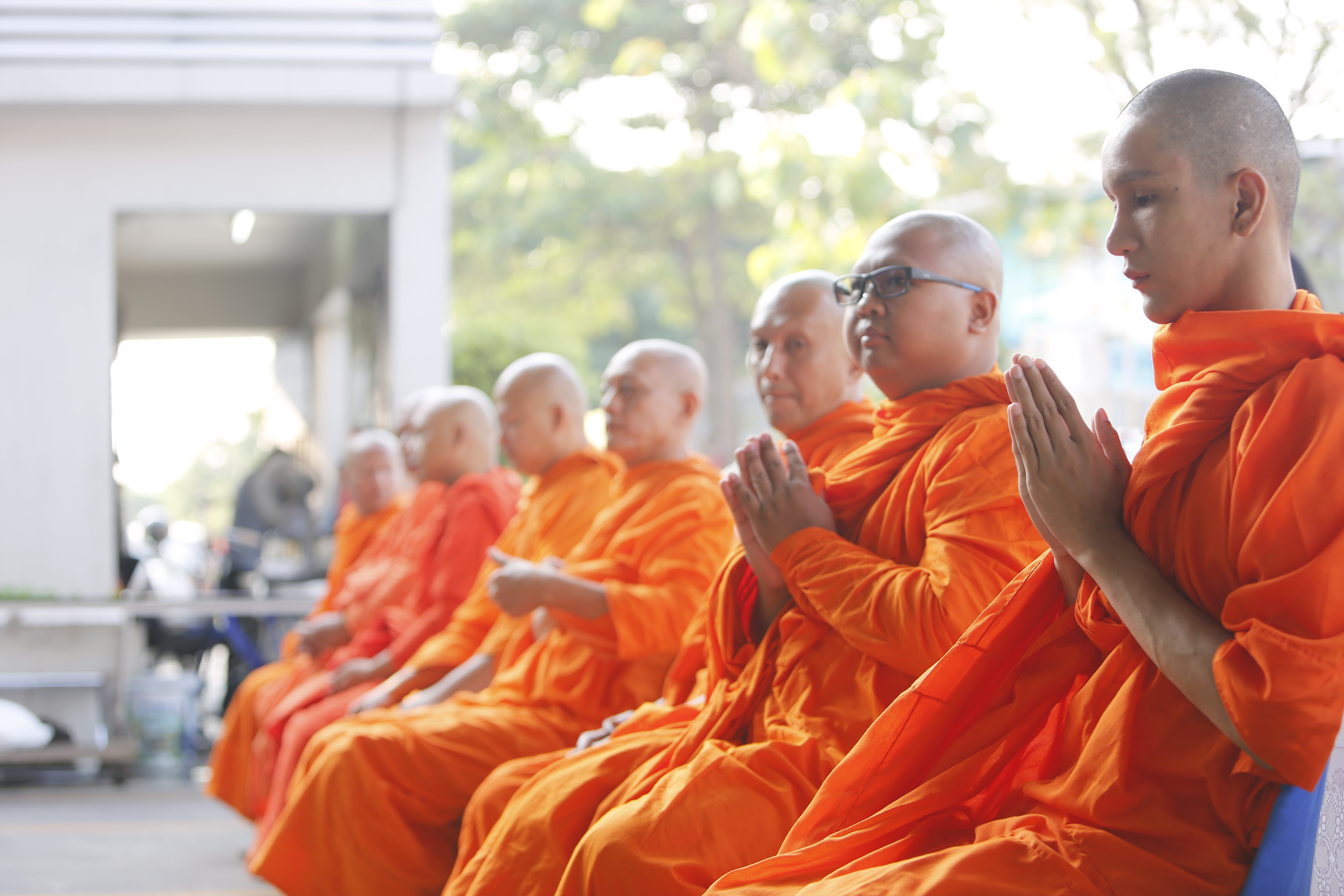 Group of Monks Sitting Near White Concrete Building