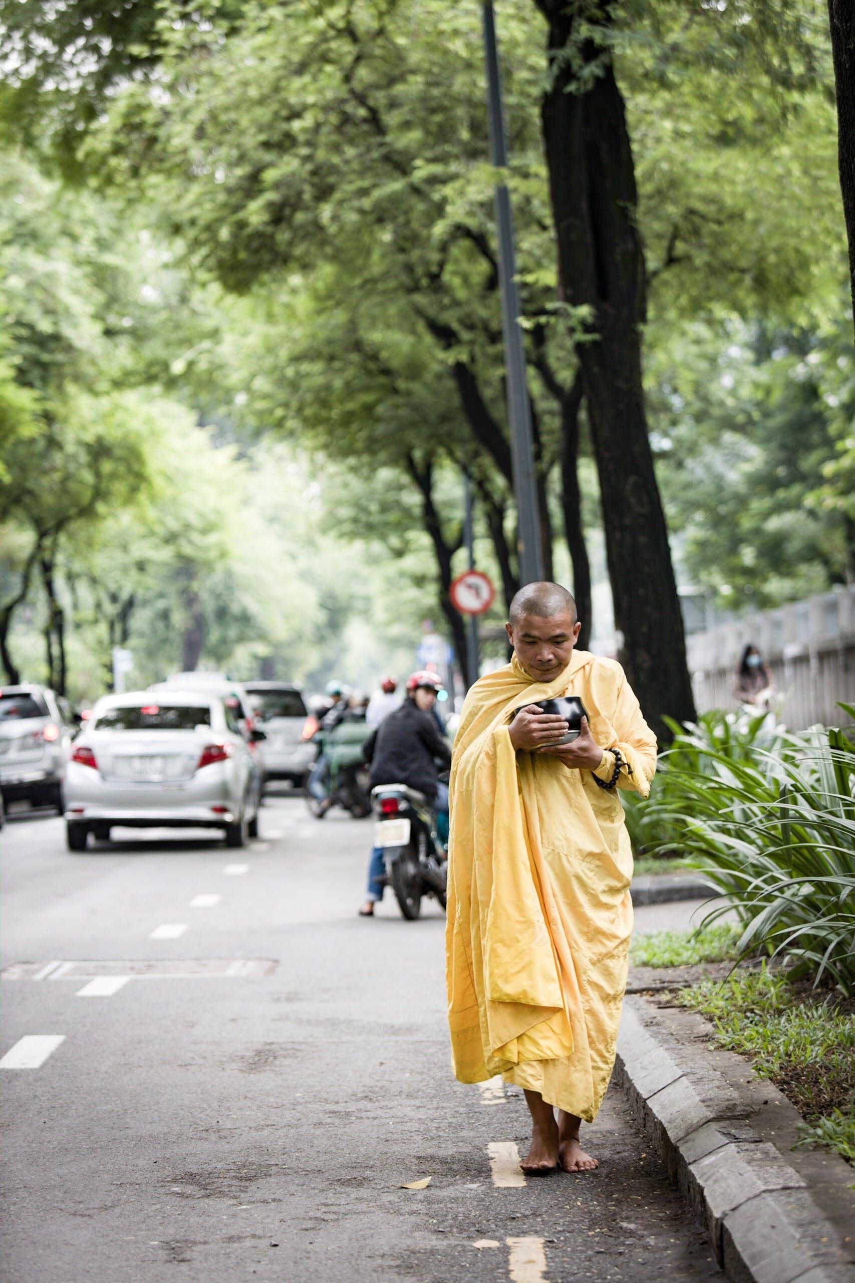 Monk Holding Bowl While Walking on Street