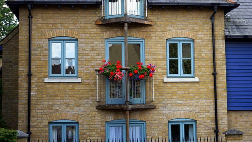 Flowers Hanged on Balcony Railing Near Windows