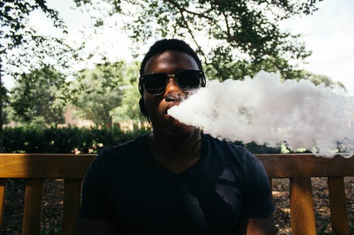Man in Black Shirt Blowing Out Smoke Under Shade of Tree