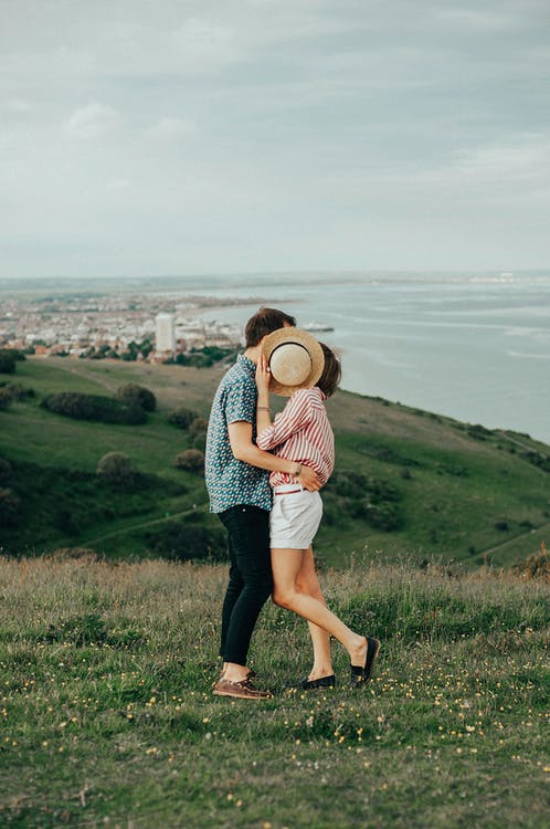 Photo of Woman and Man Hugging While Standing on Grass