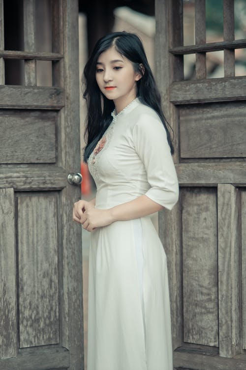Woman Wearing White Dress in Middle of Two Brown Wooden Doors