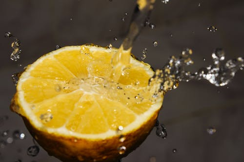 Close-up Photography of Water Poured on Slice of Yellow Lemon