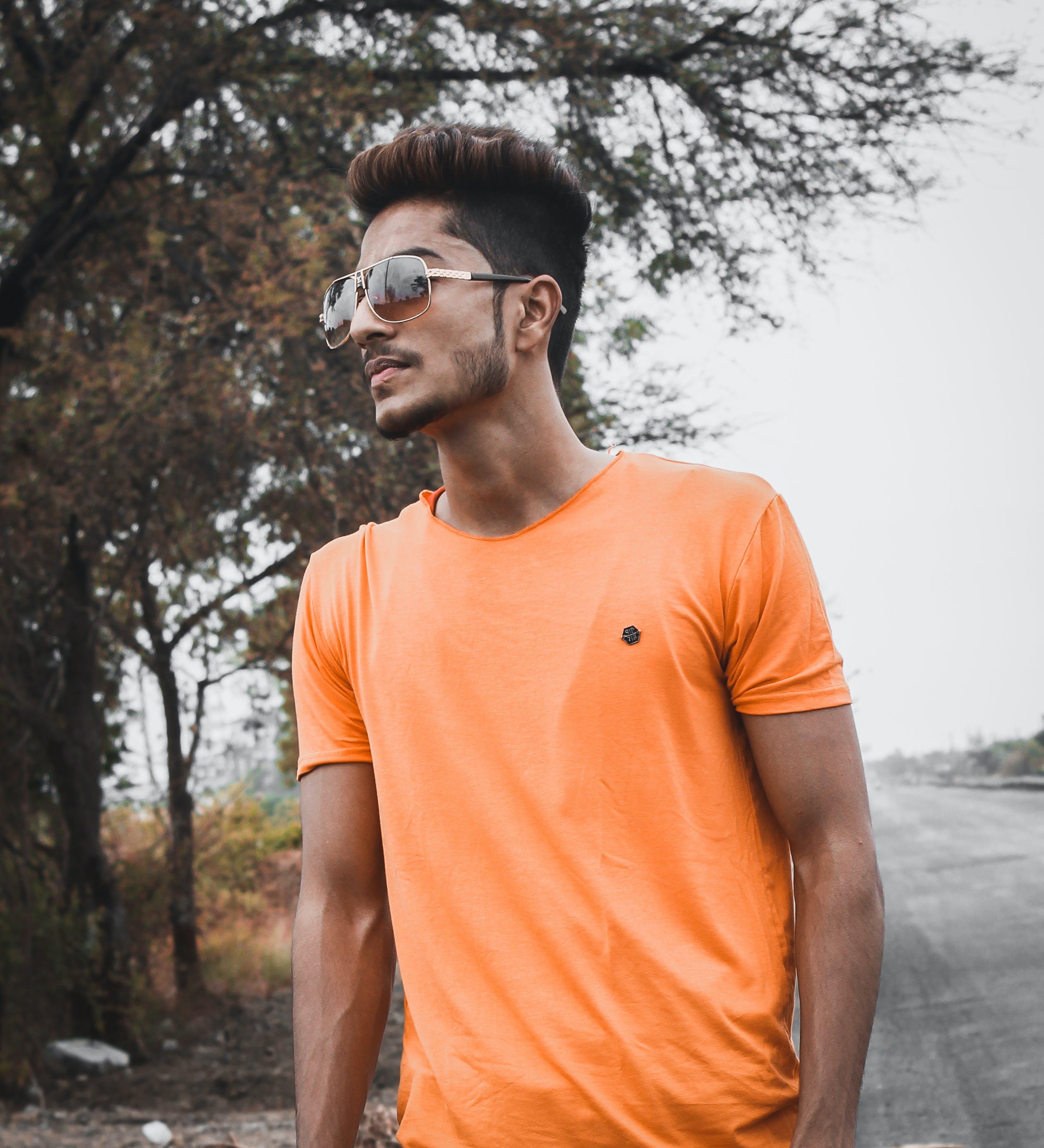 Man Standing While Wearing Orange Crew-neck Shirt Near Tree