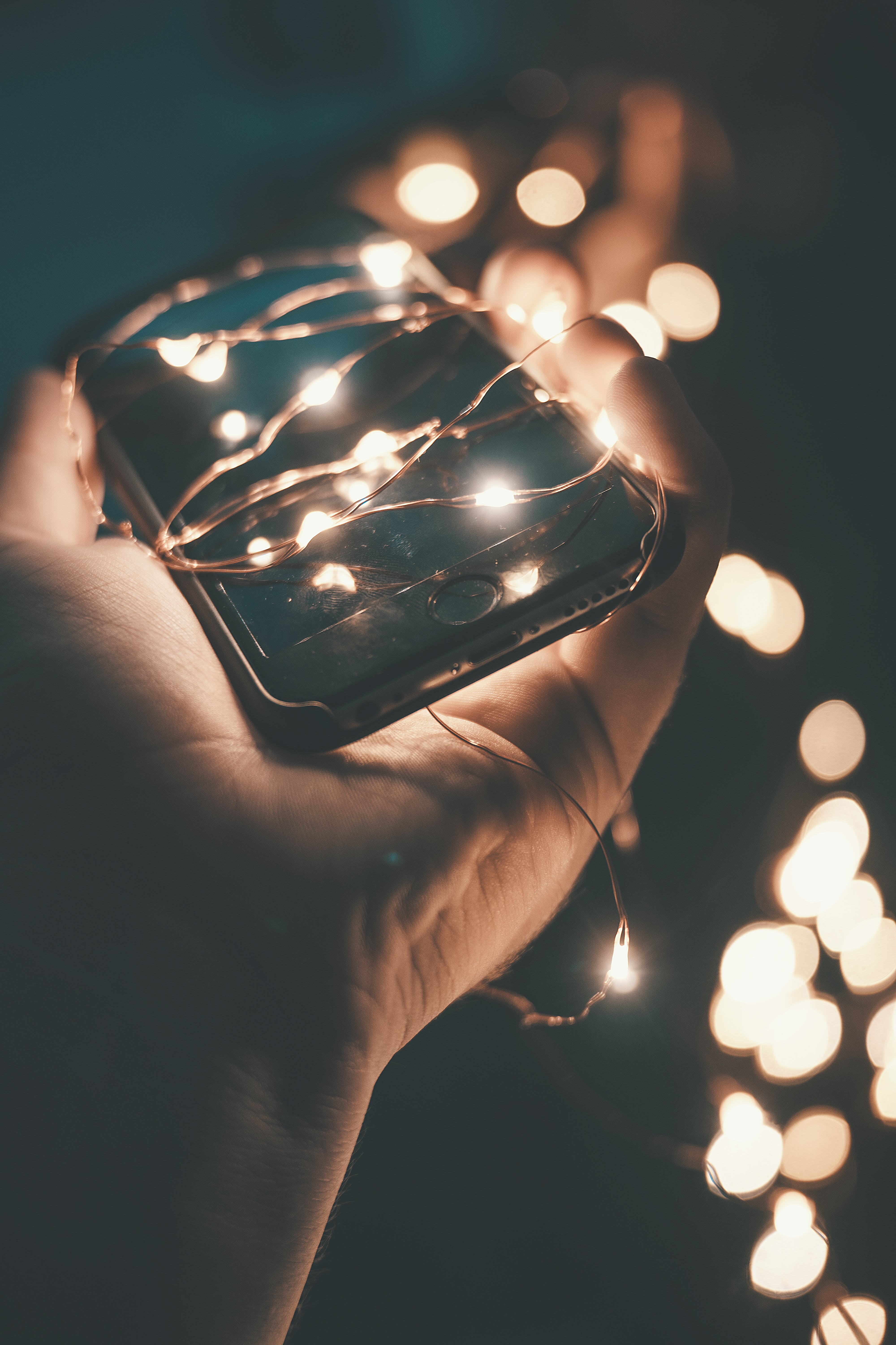 Person Holding Space Gray Iphone 6 With String Lights during Nighttime