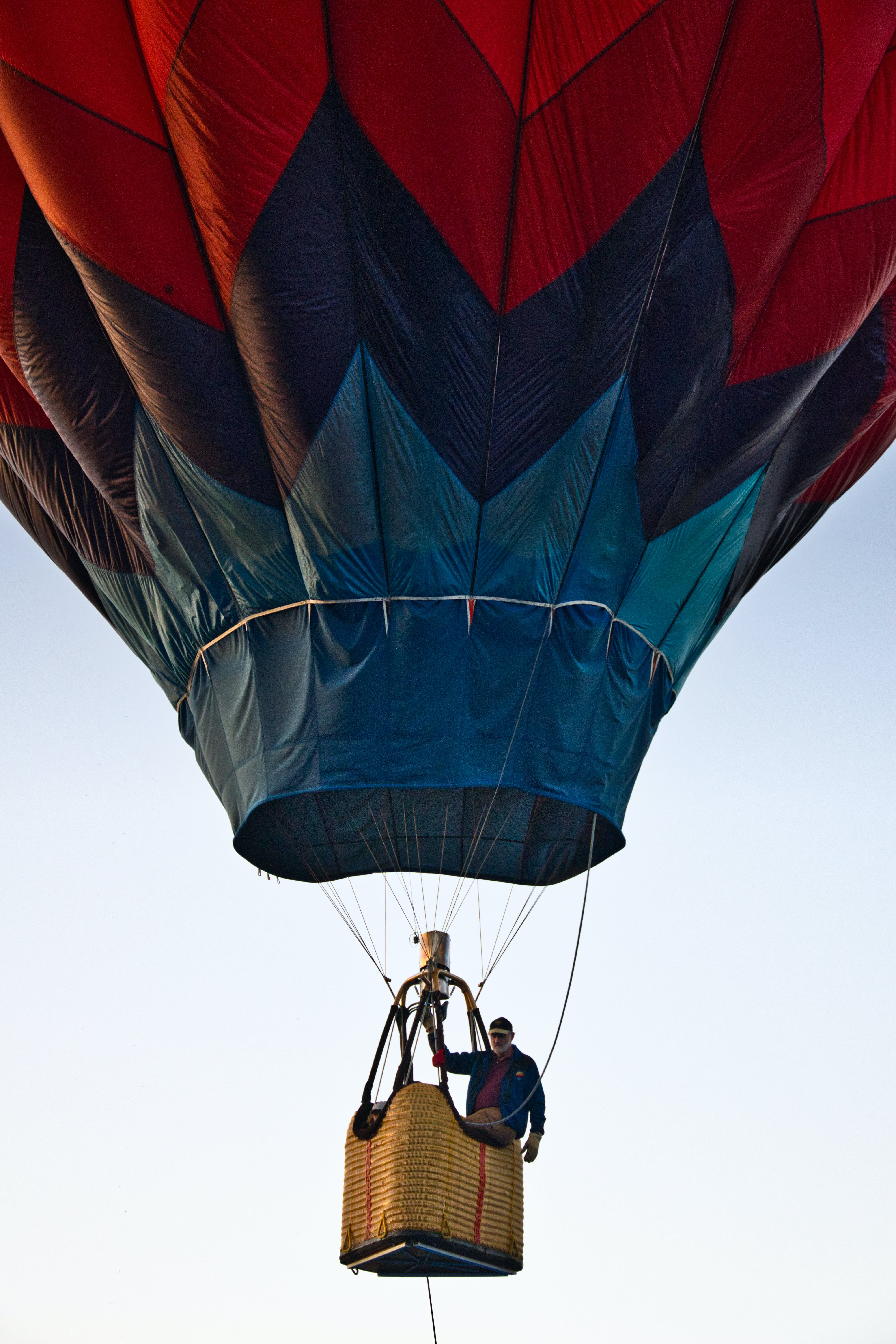 Man Riding Blue and Red Hot Air Balloon during Day