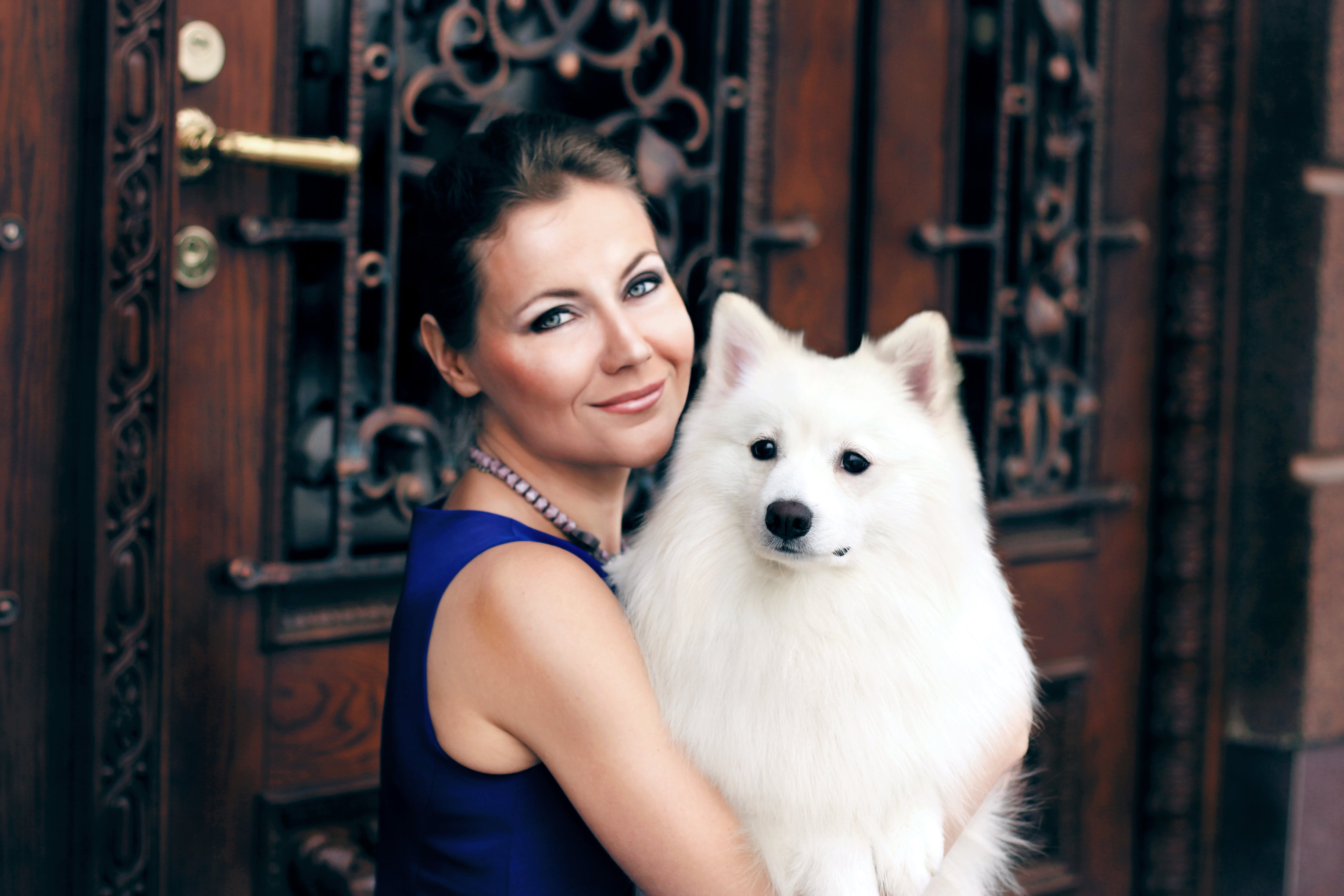 Woman Carrying Adult White Indian Spitz