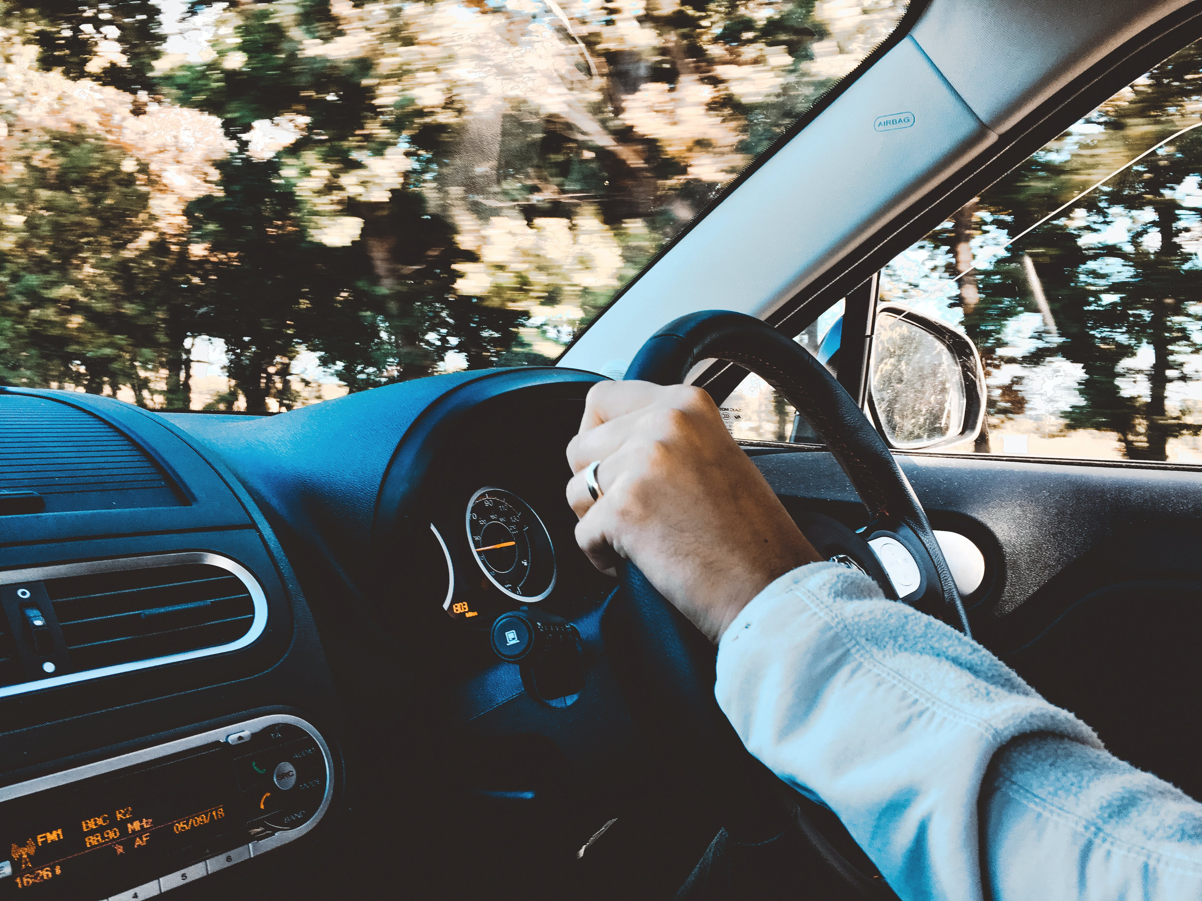 Person Holding Black Vehicle Steering Wheel