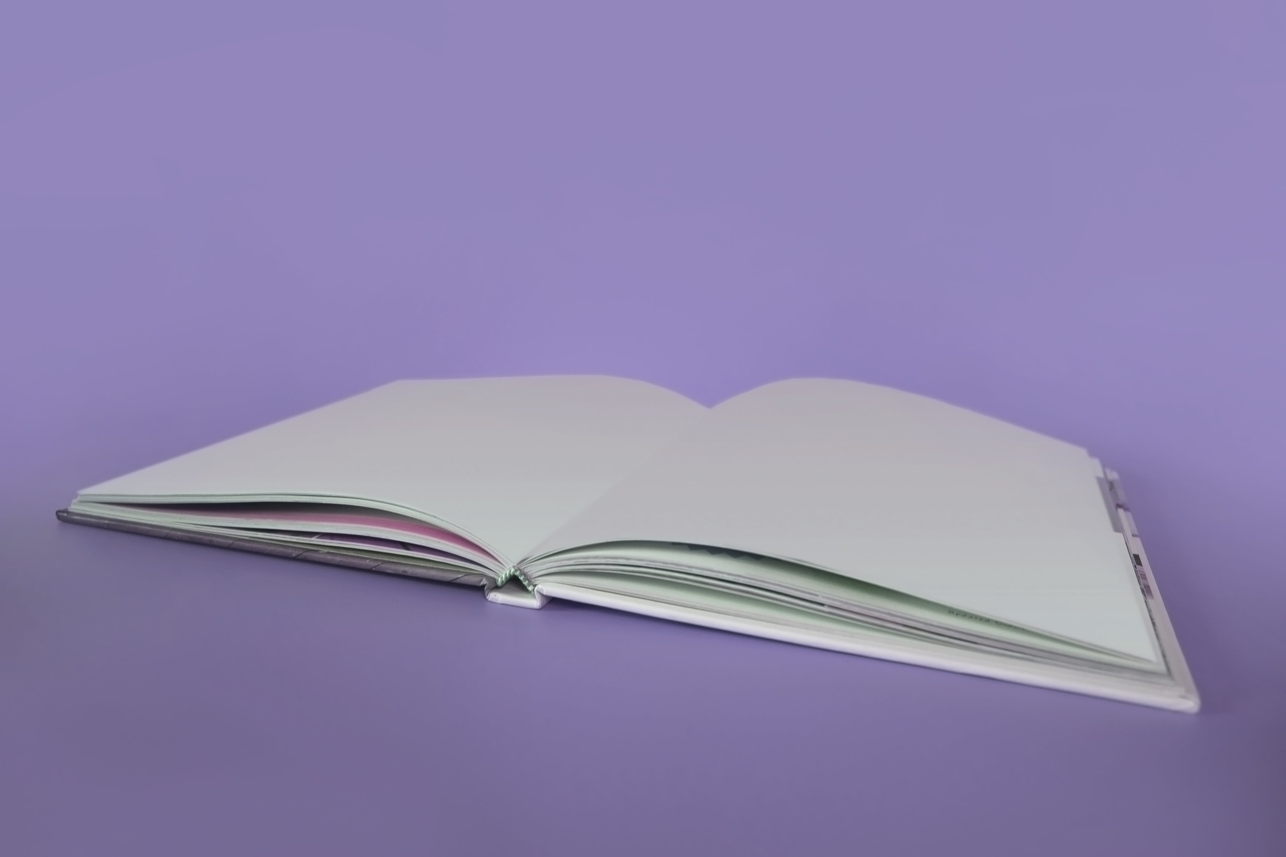 Opened Book on Purple Surface