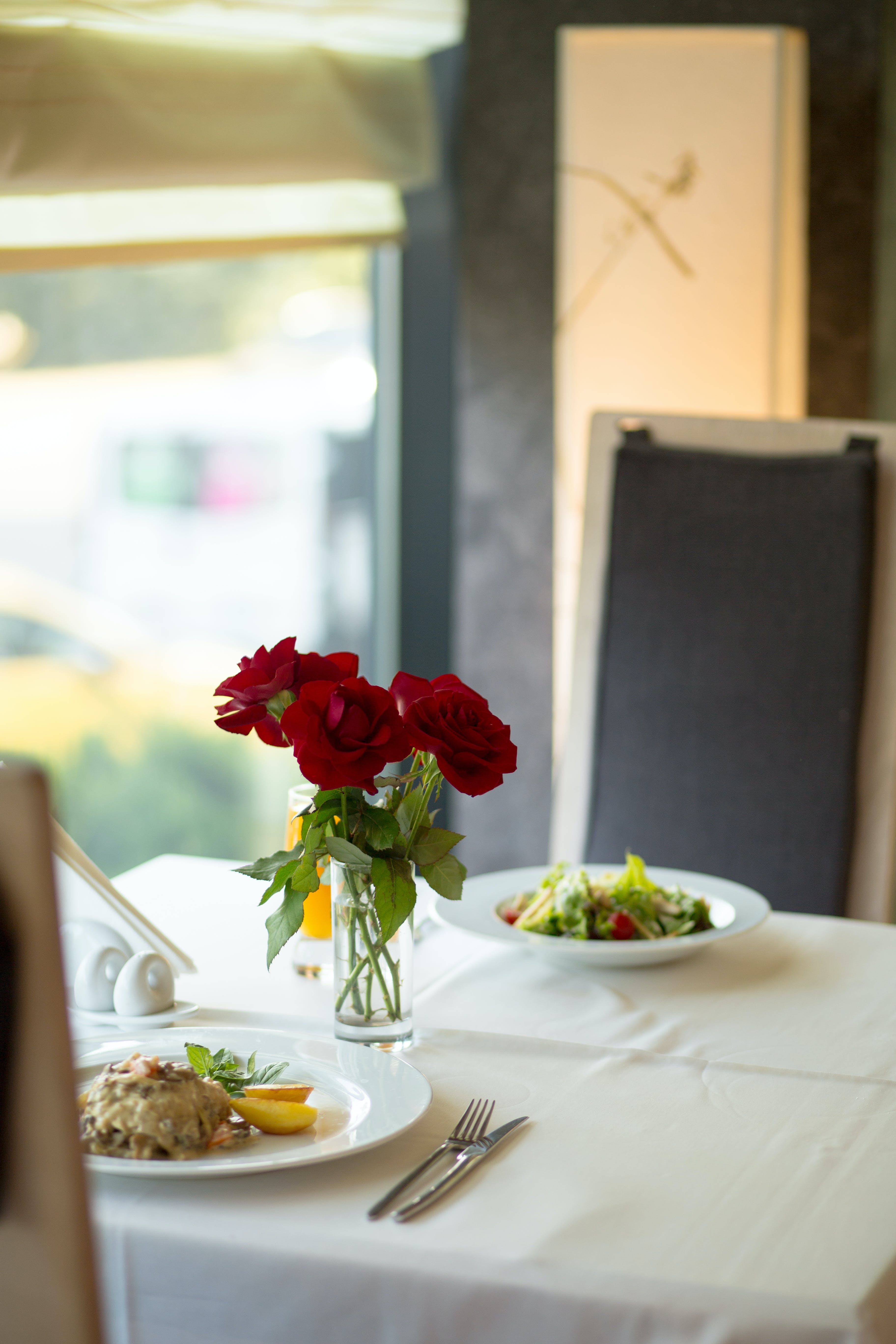Close-up Photo of Three Red Roses in Clear Vase Centerpiece