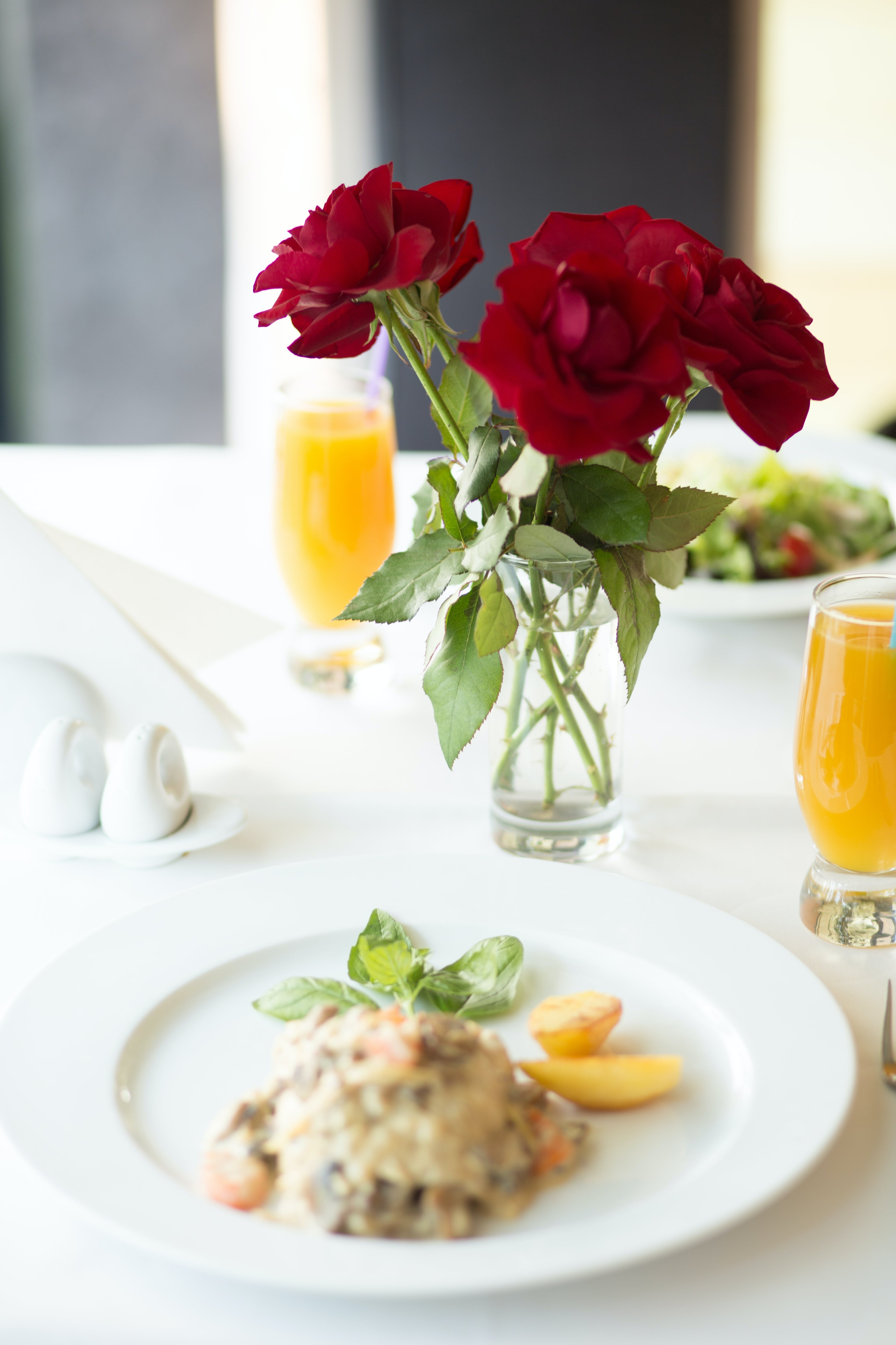 Cooked Food on Plate on Table Beside Red Rose Flowers