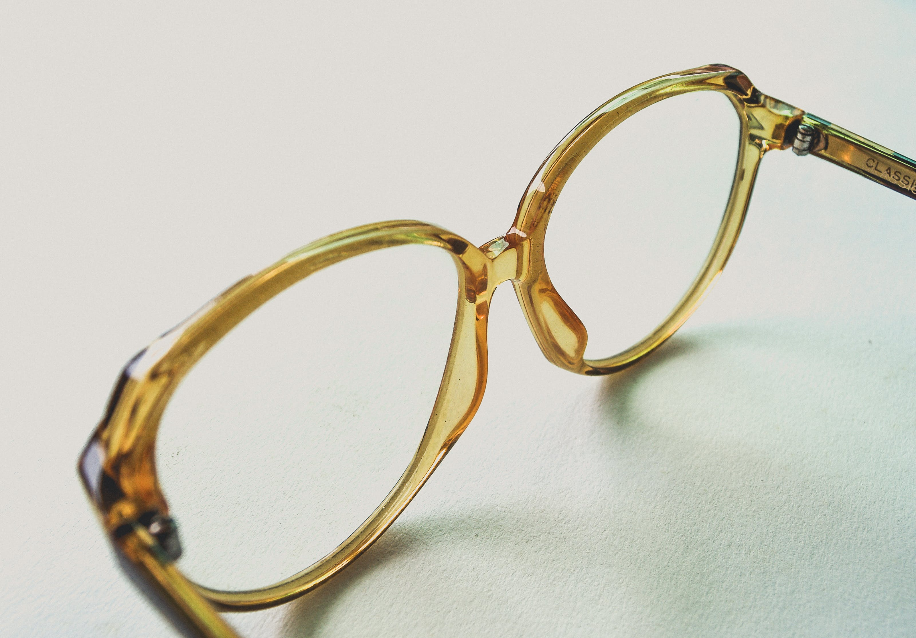 Yellow Frame Eyeglasses on White Surface
