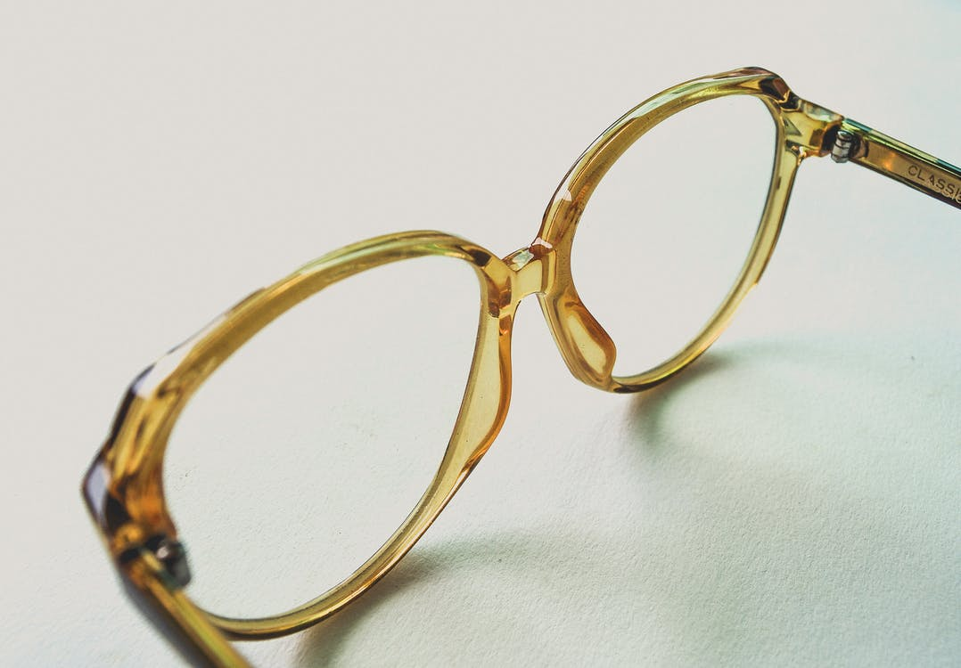 Yellow Frame Eyeglasses on White Surface