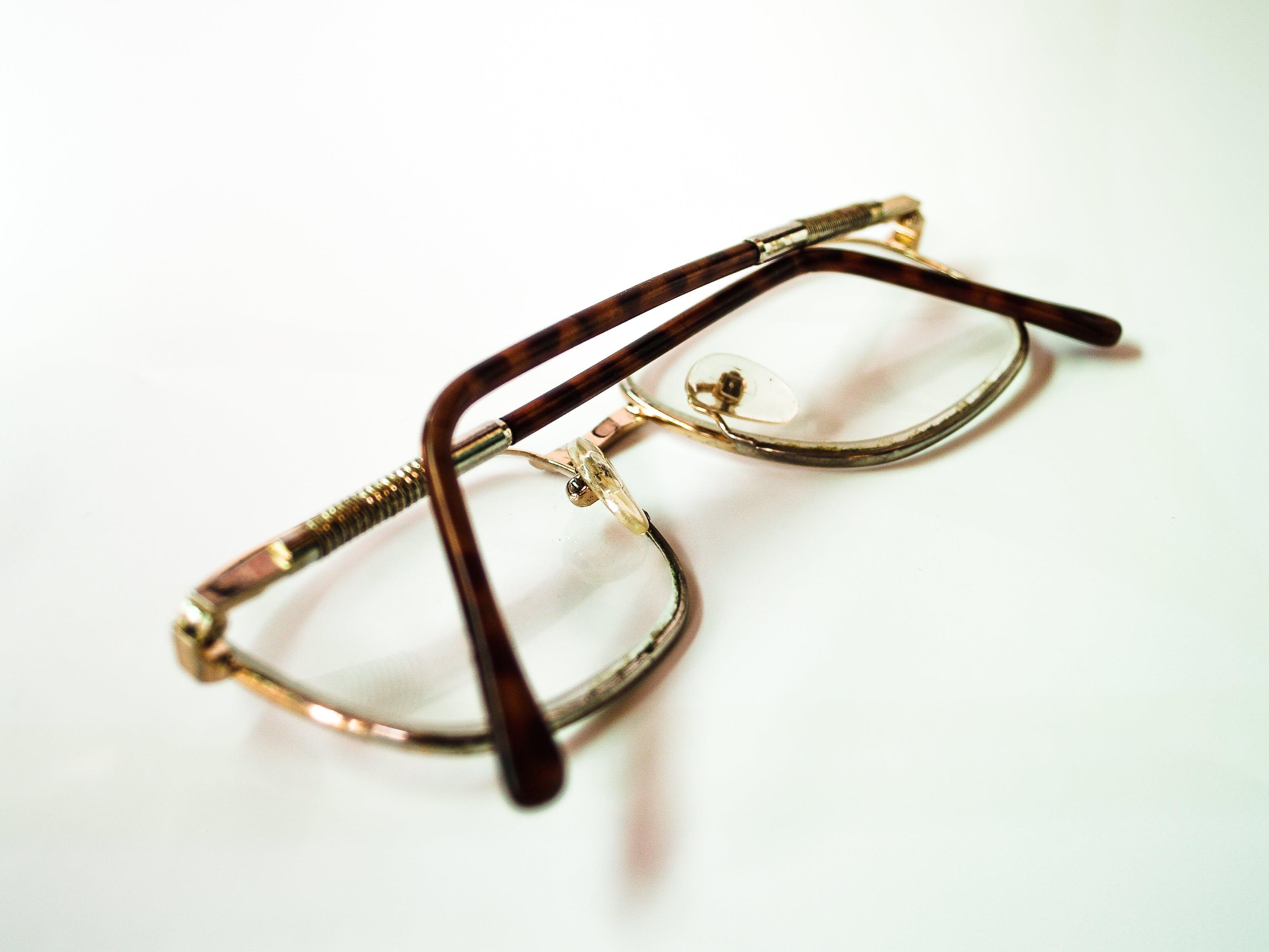 Gold Framed Eyeglasses on White Surface