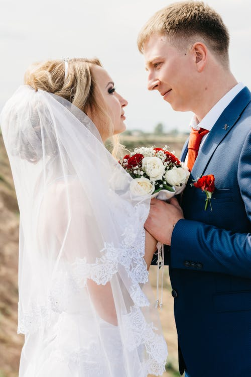 Bride and Groom Facing Each Other While Holding Hands
