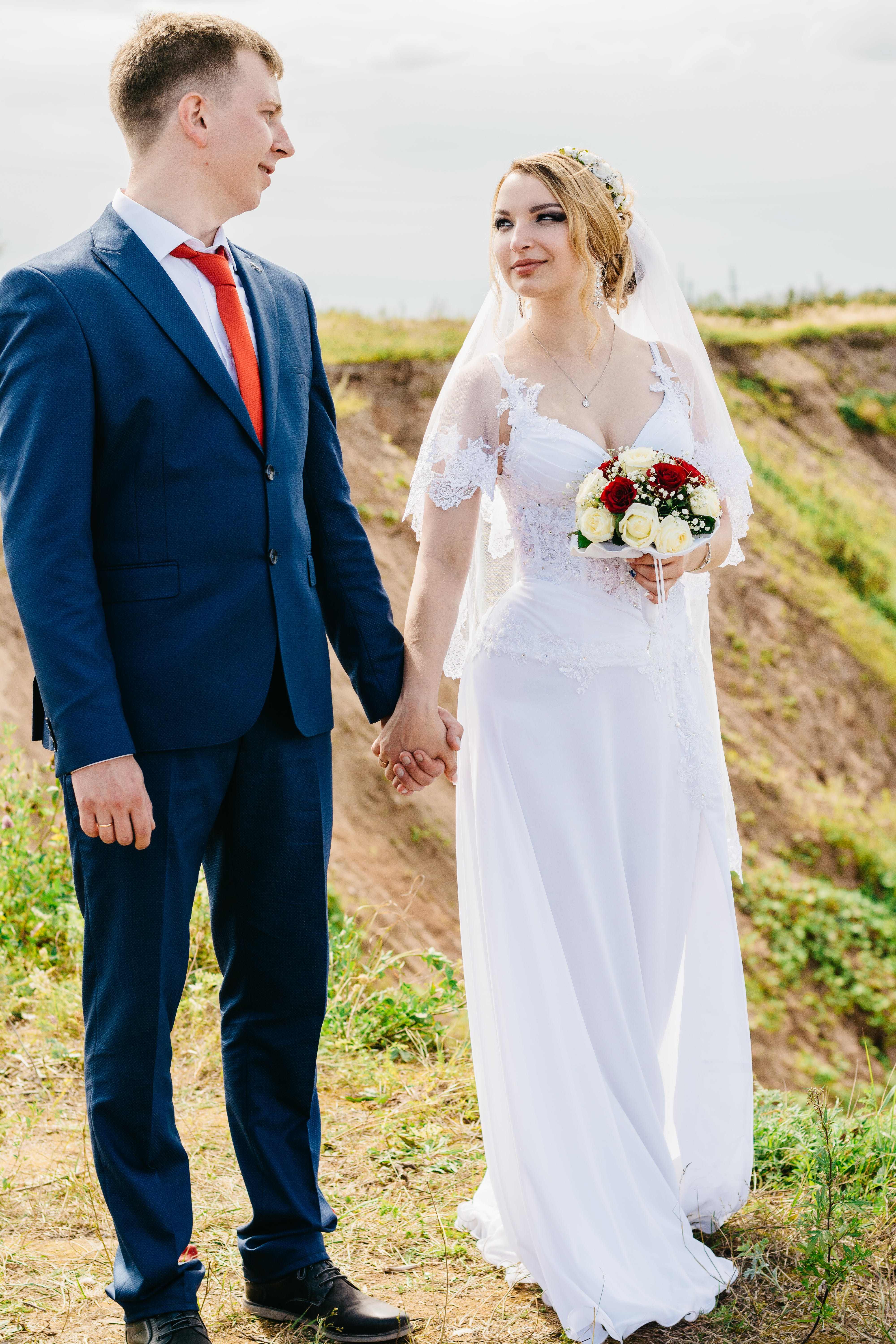 Two Man and Woman Staring and Holding Hands at Each Other While Standing on Cliff