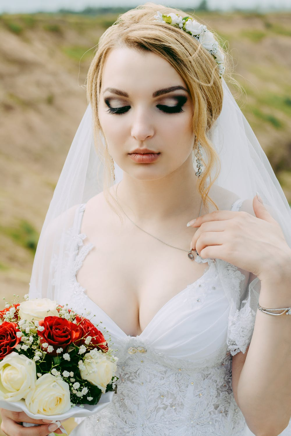 Woman wearing white lace surplice-neck wedding gown. | Photo: Pexels