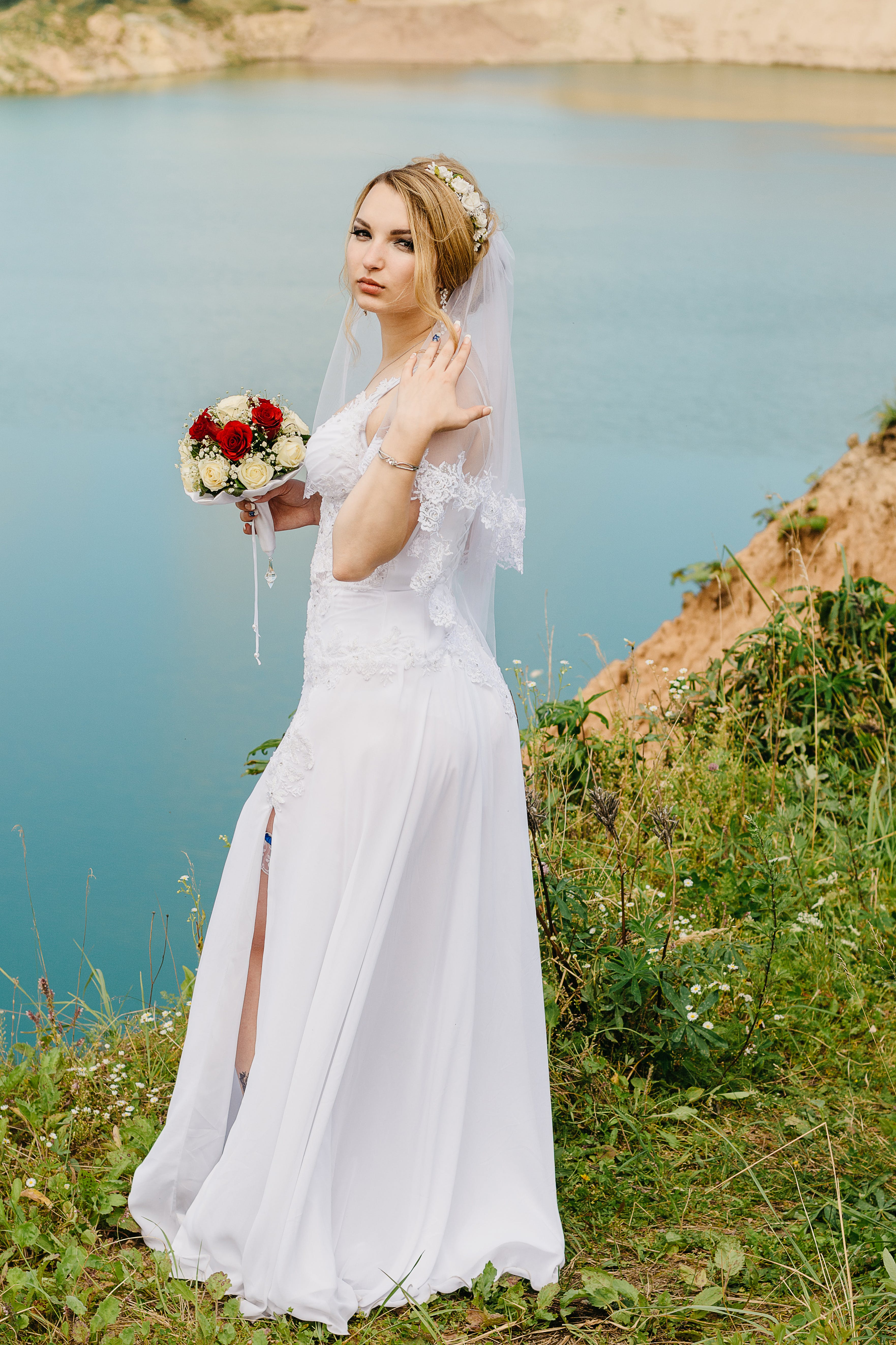 Woman Wearing White Wedding Gown While Standing on Cliff Near River
