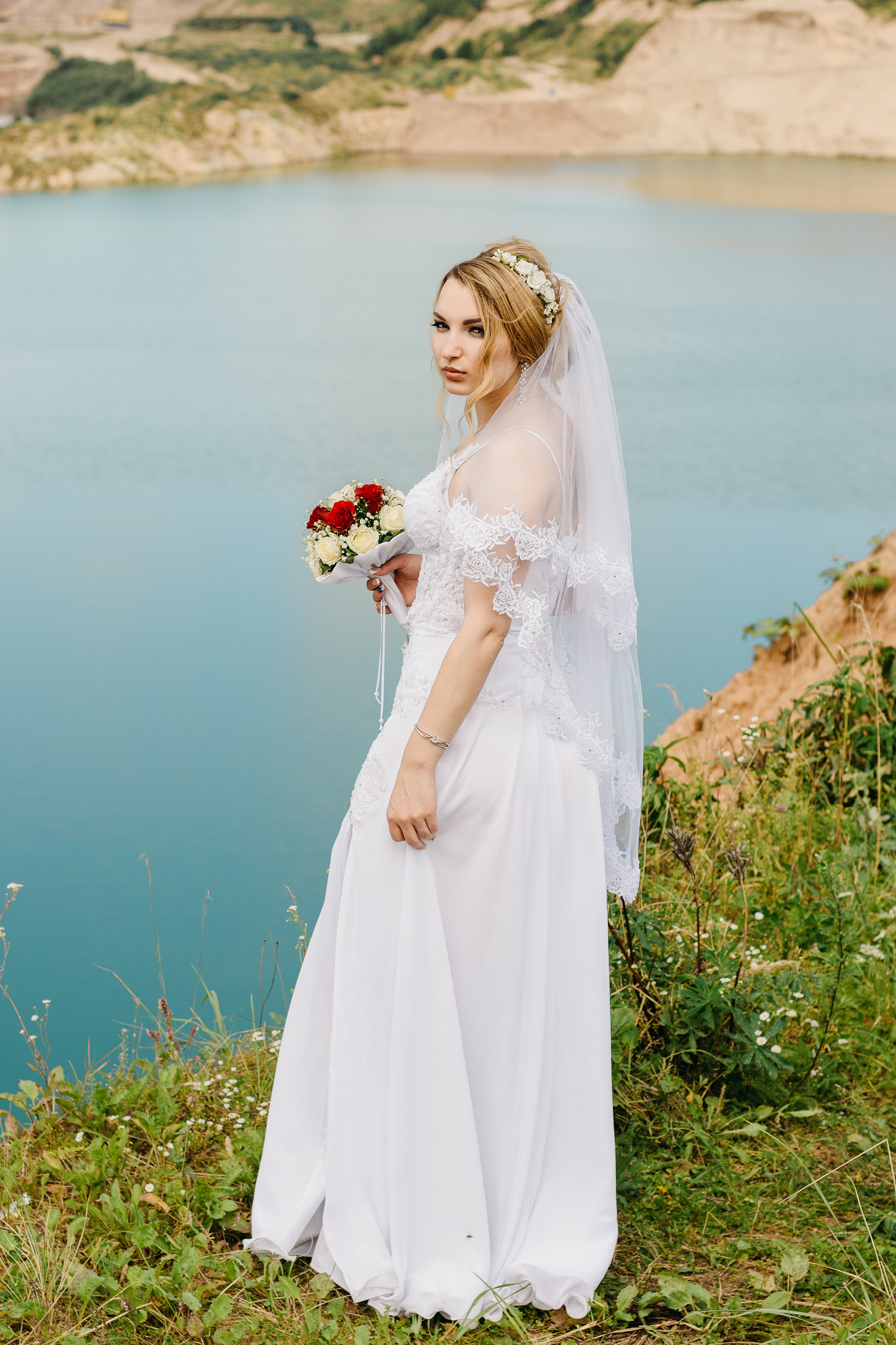 Woman in Wedding Gown Holding Bouquet in Front of Lake