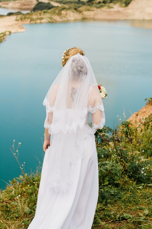 Woman Wearing White Lace Wedding Gown Standing Near the Cliff