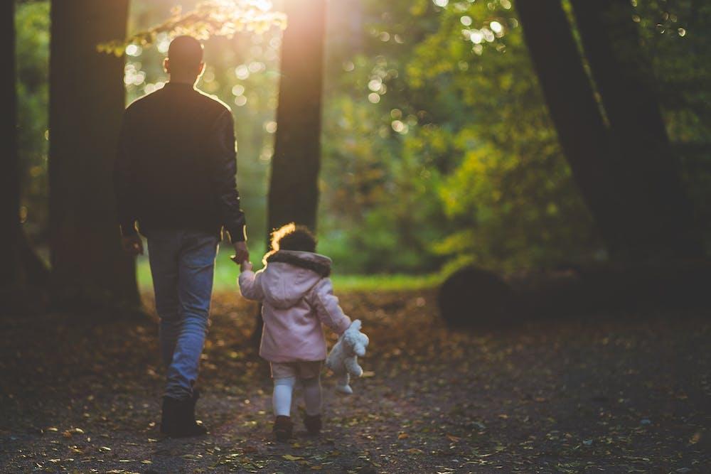 Man holding a child.   Photo: Pexels