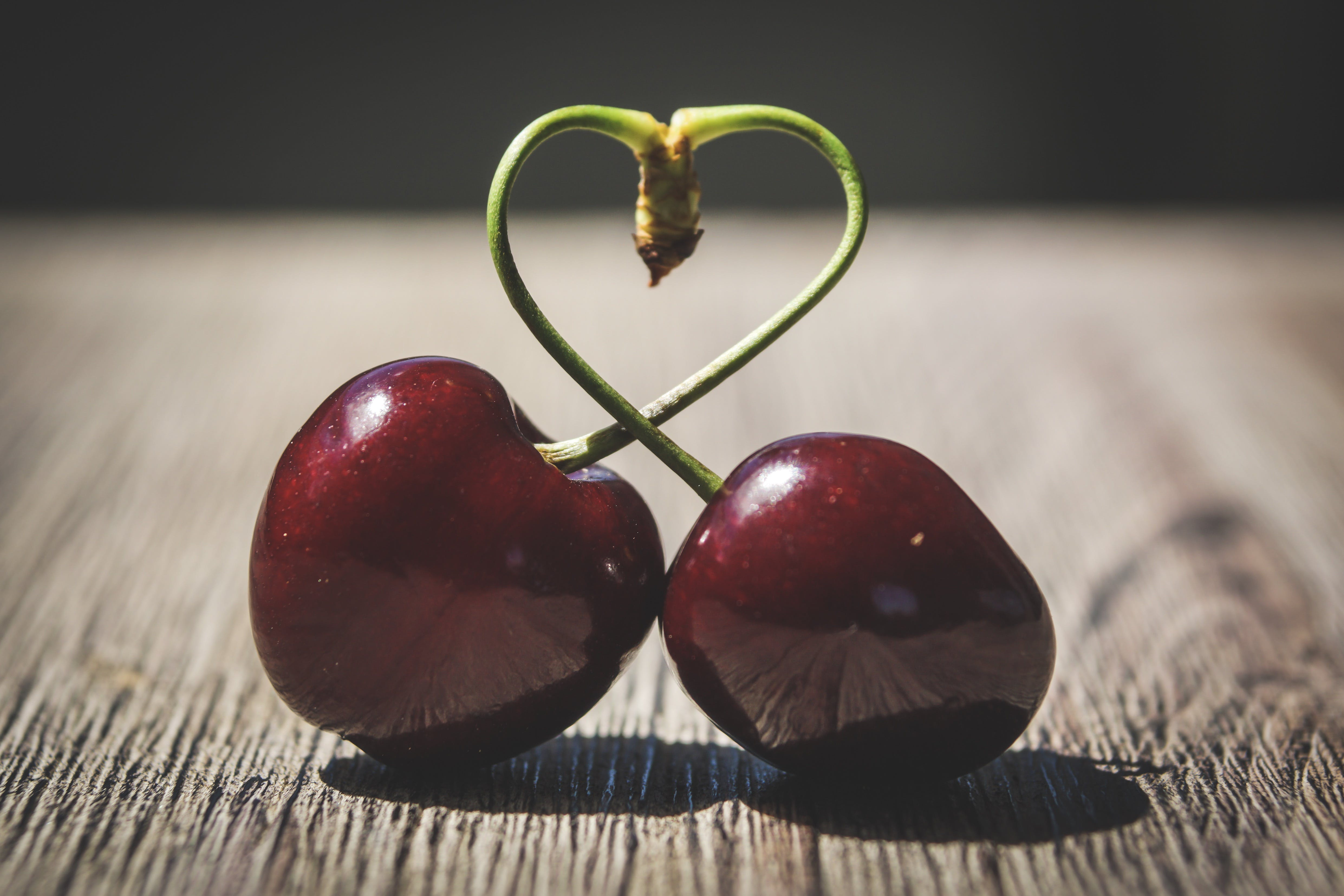 Two Red Cherries on Brown Surface