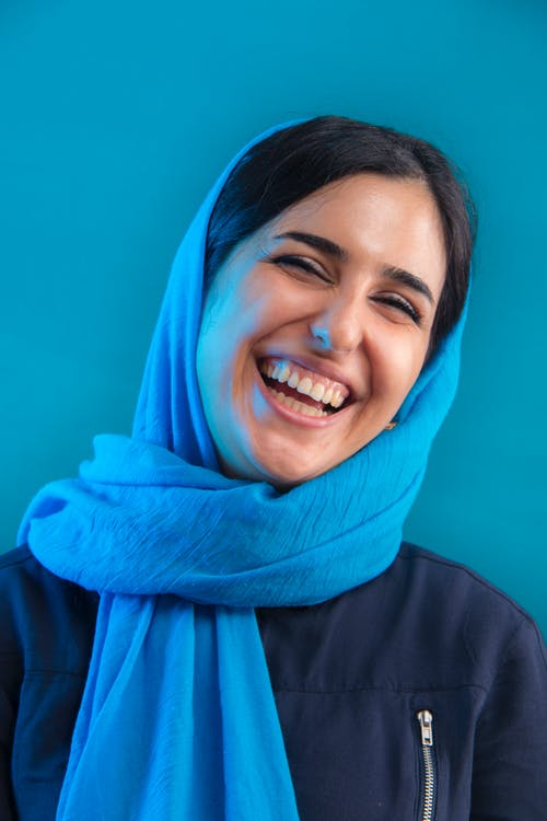 Woman Leaning on Blue Wall While Smiling