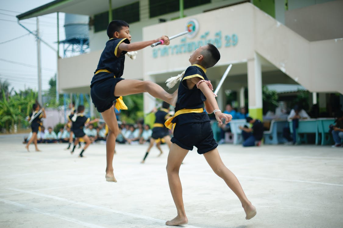 Photography of a Boy Kicking Another Boy